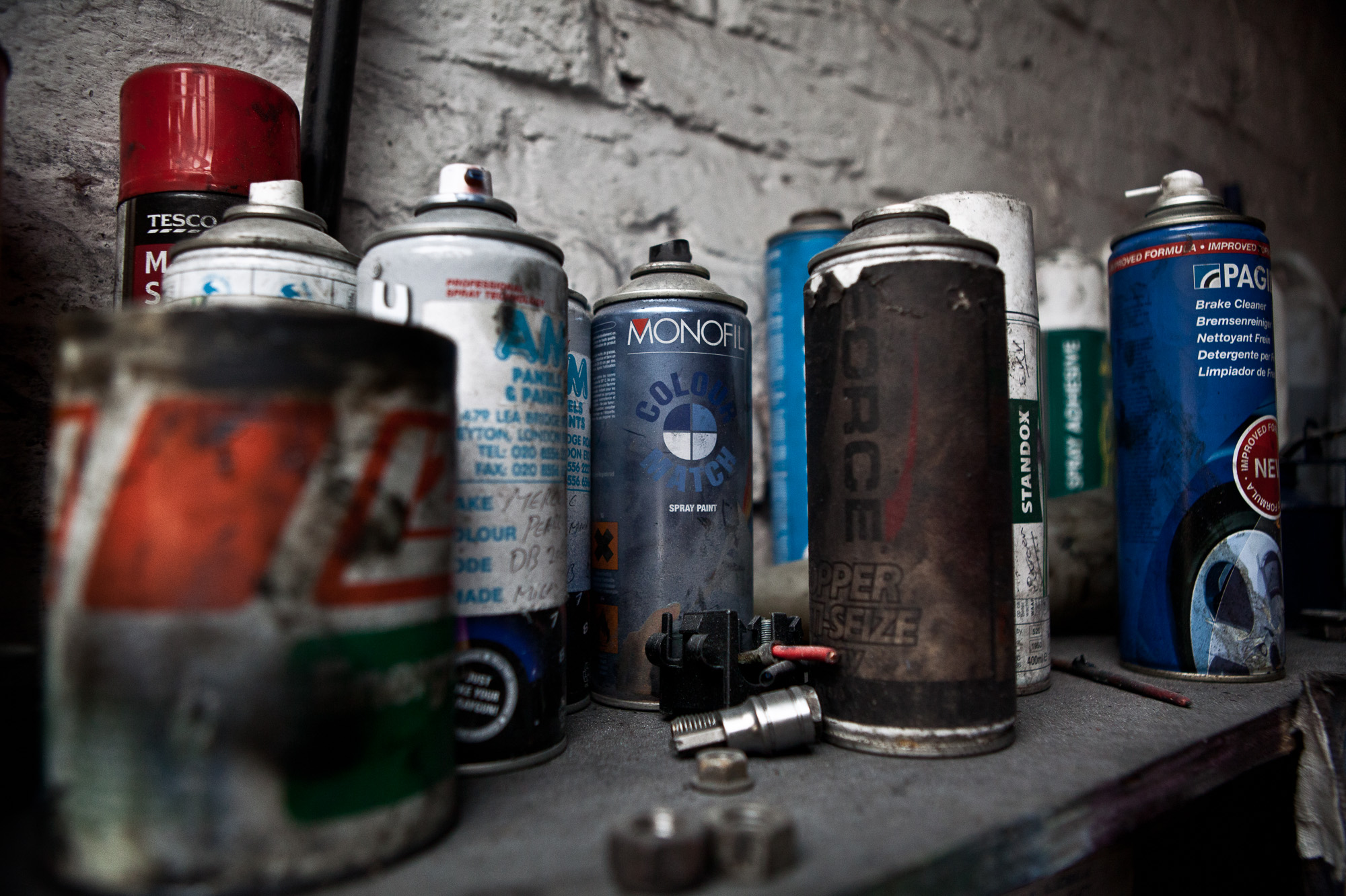 Cans of spray paint and lubricating oil are randomly placed on a shelves all over the garage within easy reach of the main working area, with nothing being wasted and everything put to good use, as the business runs on a very tight margin.