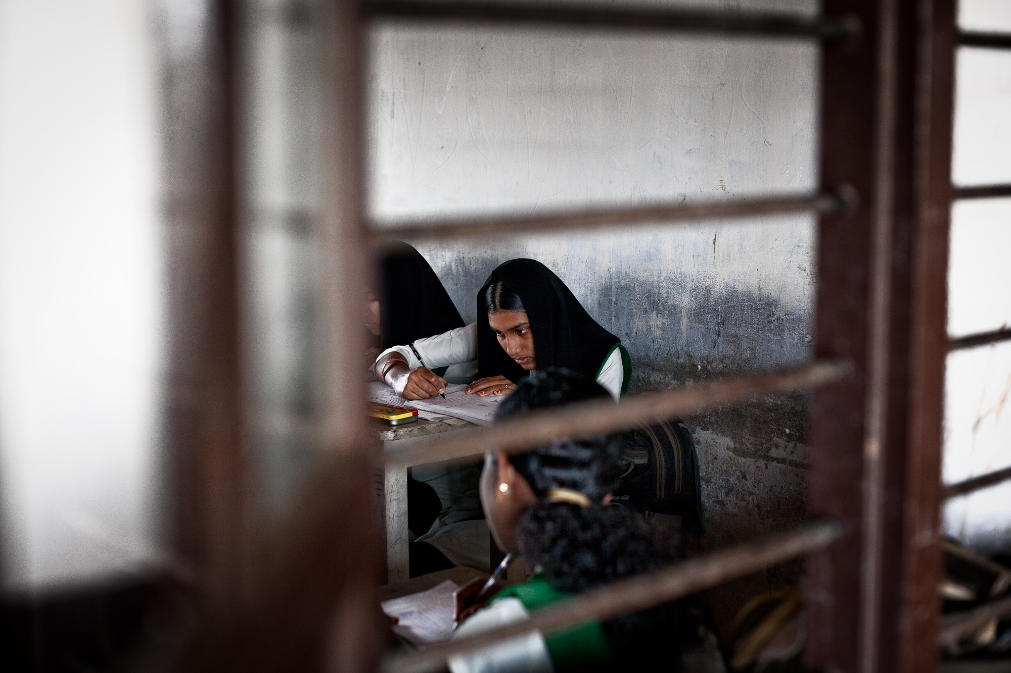 A girl from 10th standard takes an exam in her classroom at the Roman Catholic High School.  The estate provides scholarships for those over the age of 14 to remain in school and obtain a good education. Additional incentives are provided for girls such as giving them bicycles, and other school accessories.  Historically Muslim girls tended not to extend their education after this age, however these improvements have enabled this group to remain in education for longer and seek higher status employment.