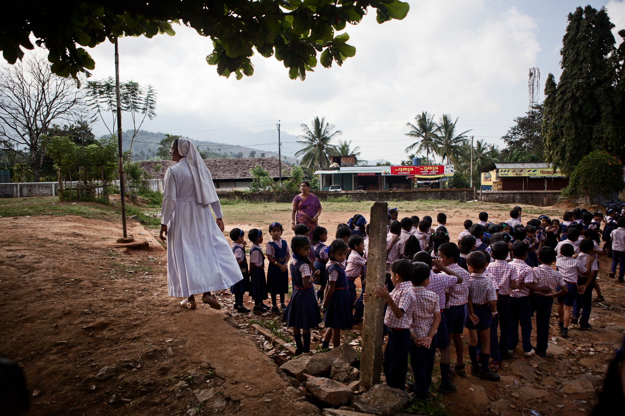 Sister Joshma finishes addressing the morning assembly at the Roman Catholic Lower Primary school (RCLP) before leading the children back to the classroom. Estate workers children, like their older brothers and sisters at the high school, are provided with free uniforms and bags from the tea estate as part of the welfare benefits.  This alleviates the pressure financially for many of the workers, especially women, as they are lowly paid.