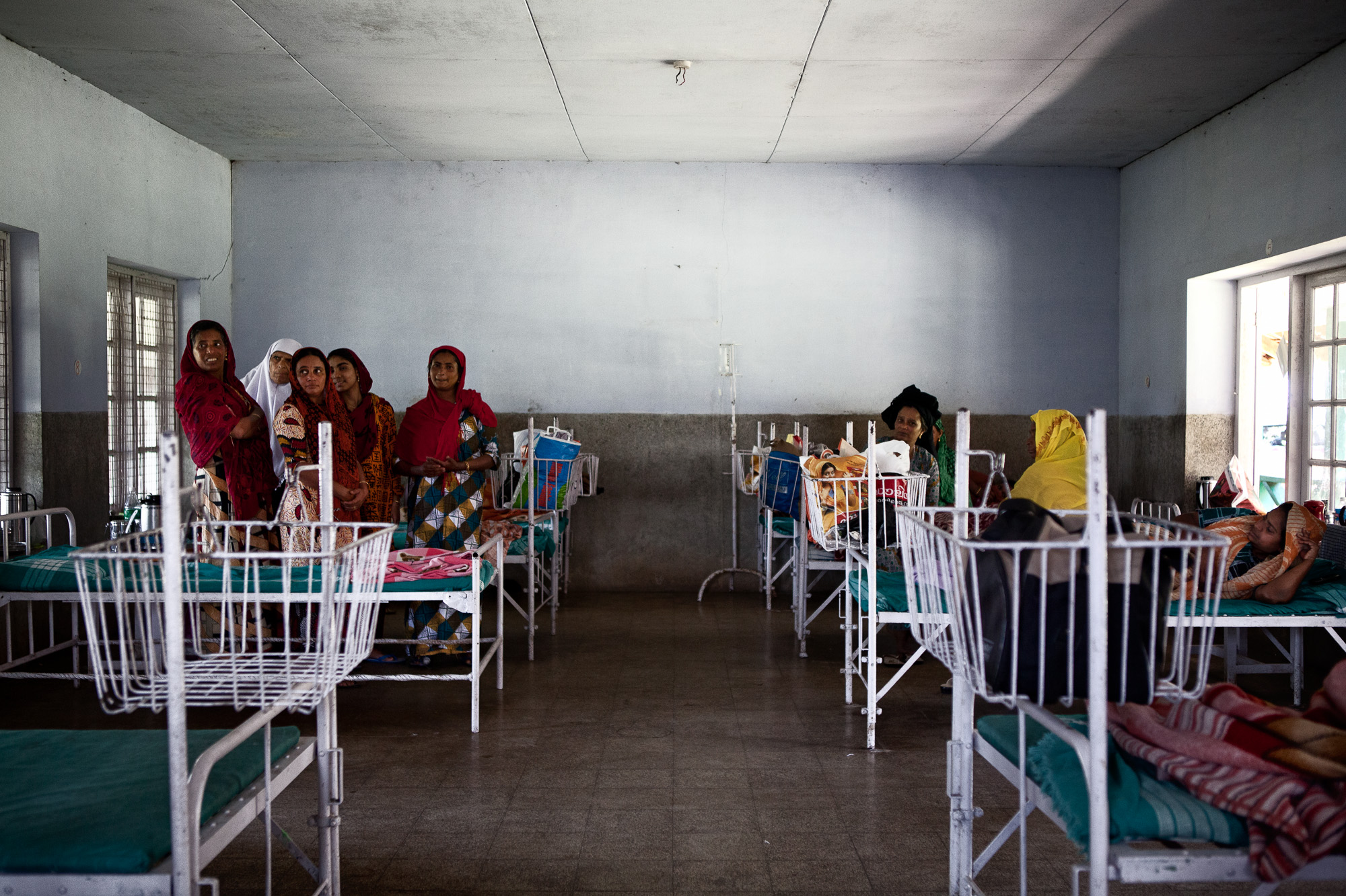 "Women talk in one of the two wards at the estate run hospital. On sight are 2 doctors and nursing staff, as well as an operating theatre and x-ray equipment. This ensures the physical welfare of all estate families and is provided free of charge.   The Kerala state government has been at the forefront of family planning initiatives bring the birth rate down to that of the United Kingdom and in fighting domestic violence with the introduction of the ""Domestic Violence Act 2005"" aimed at safeguarding women."