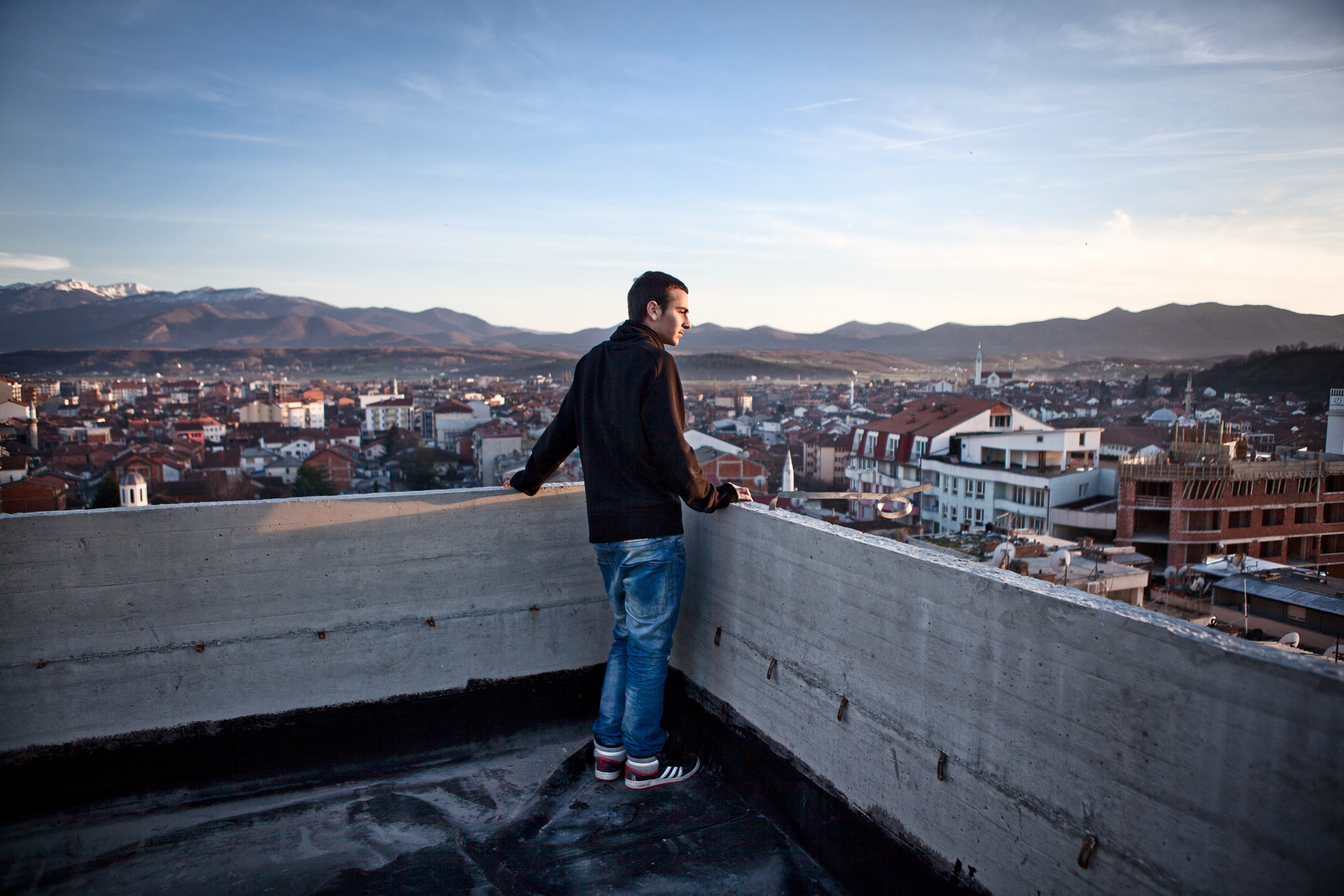 Pëllumb Rraci, 16 years old, high school student, looks out over the city of Gjakova from the top of an unfinished building.   Even with the prospect of probable unemployment, he remains highly motivated and optimistic in following his father's footsteps of becoming an accountant. Kosovo has a highly educated young population with enormous potential.