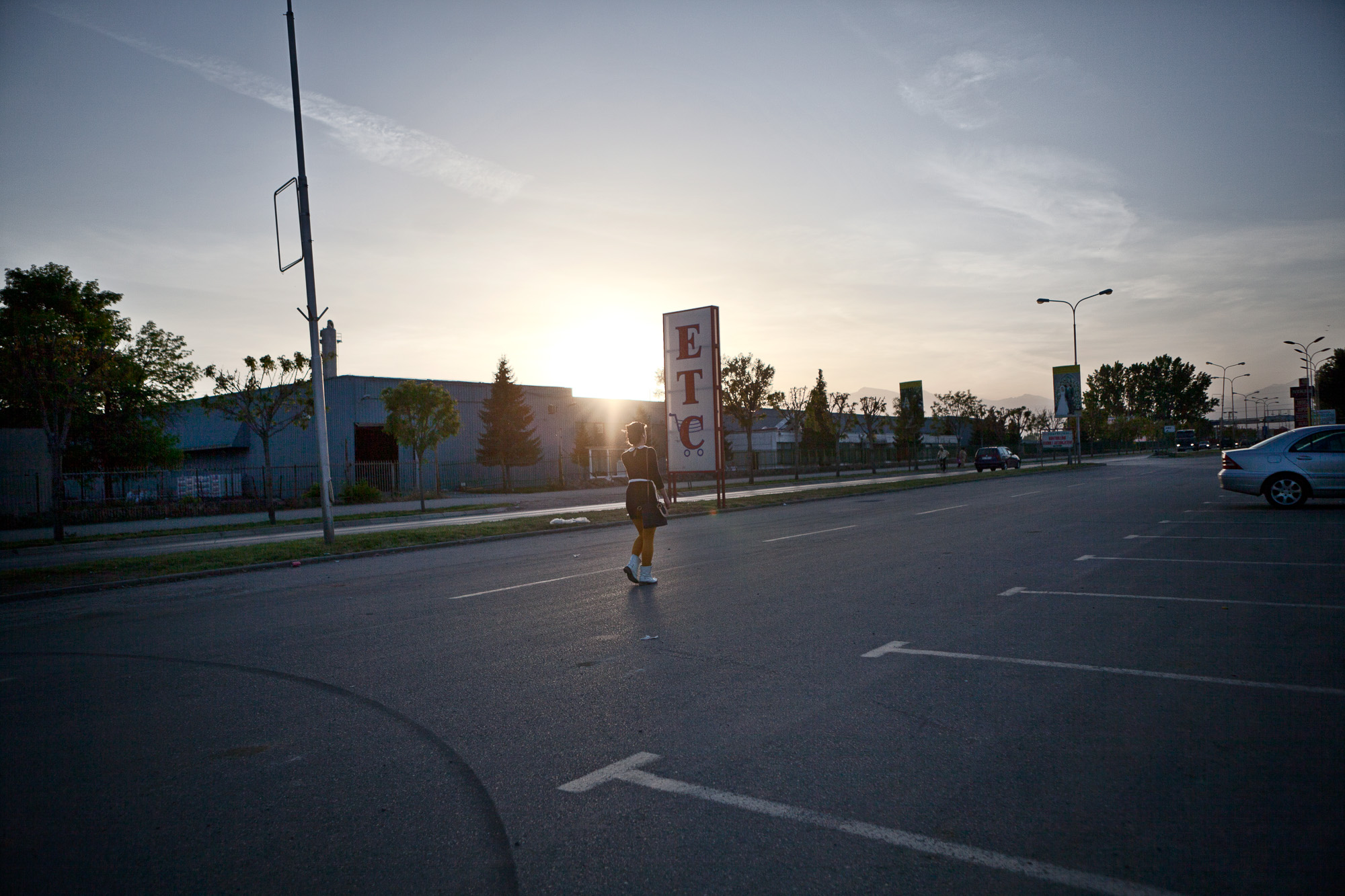 At twilight, a young woman walks down an empty street in the old industrial area of Gjakova, now lined with empty buildings.  She, like many of her age group, see the opportunities offered abroad but is unable to seize them due to the lack of visa liberalization. Although part of Europe, Kosovo remains one of the most isolated countries on earth due to its limited international sovereignty and its passports not being recognized universally.   This requires citizens to obtain a travel visa, even within neighboring states.   This adds another hurdle for the opportunities of youth.