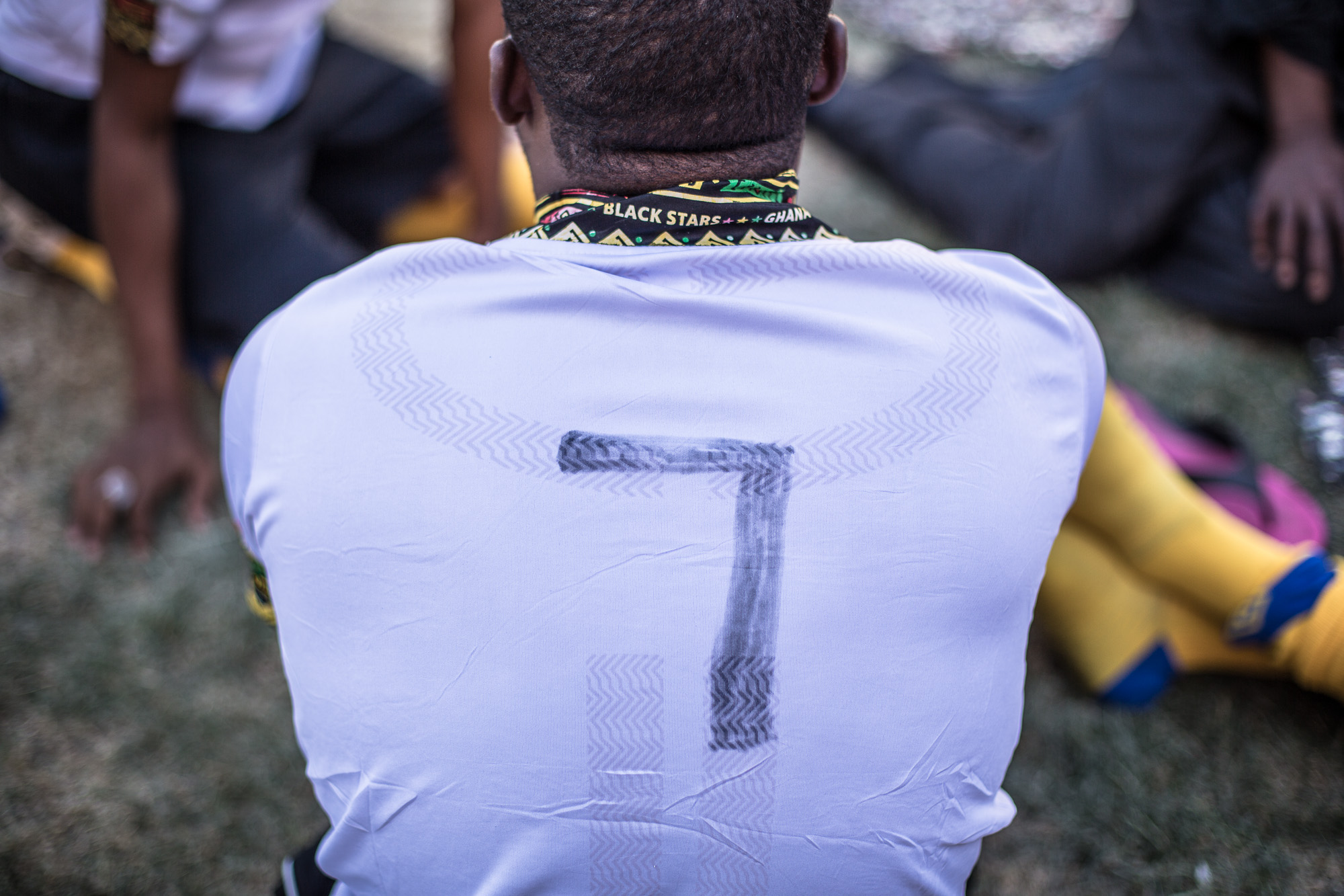 A player from team Ghana, with his marker drawn number 7, sits amongst his team pitch-side after a match.  While some teams will have been able to obtain sponsors for kit as well as travel costs to participate in the tournament, other will not.   Ghana only just managed to attend with enough players to compete, meaning other areas, such as kit were not a priority.  Each nation depends on its own charitable donations to fund teams who can attend. For some nations this process is easier than others.