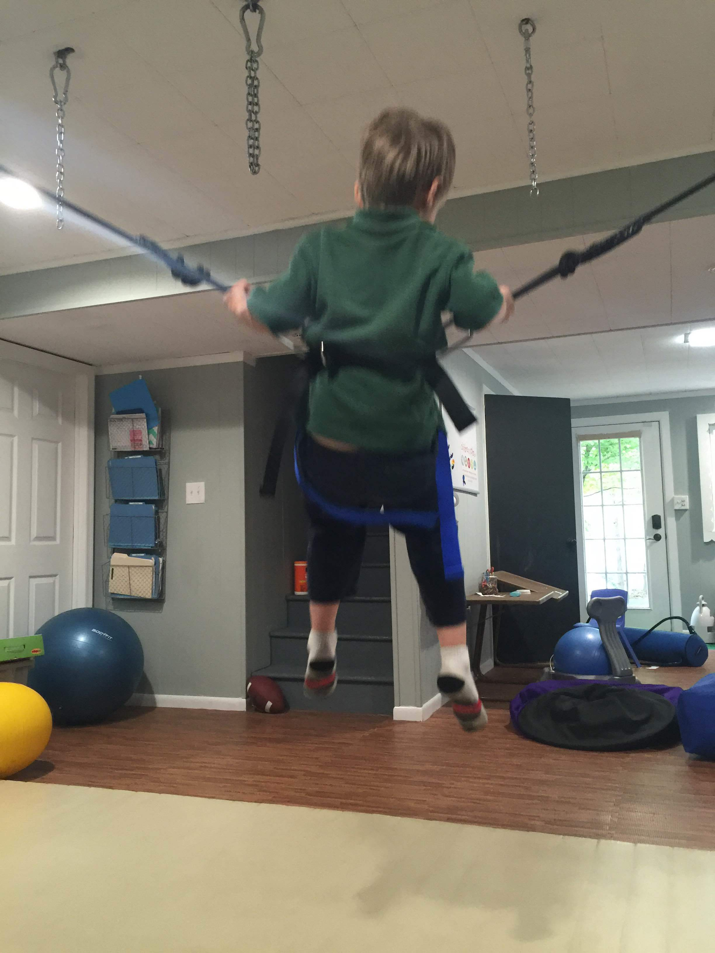 Using bungees with the harness to provide intense vestibular and proprioceptive input for self-regulation-- its also a ton of fun :)