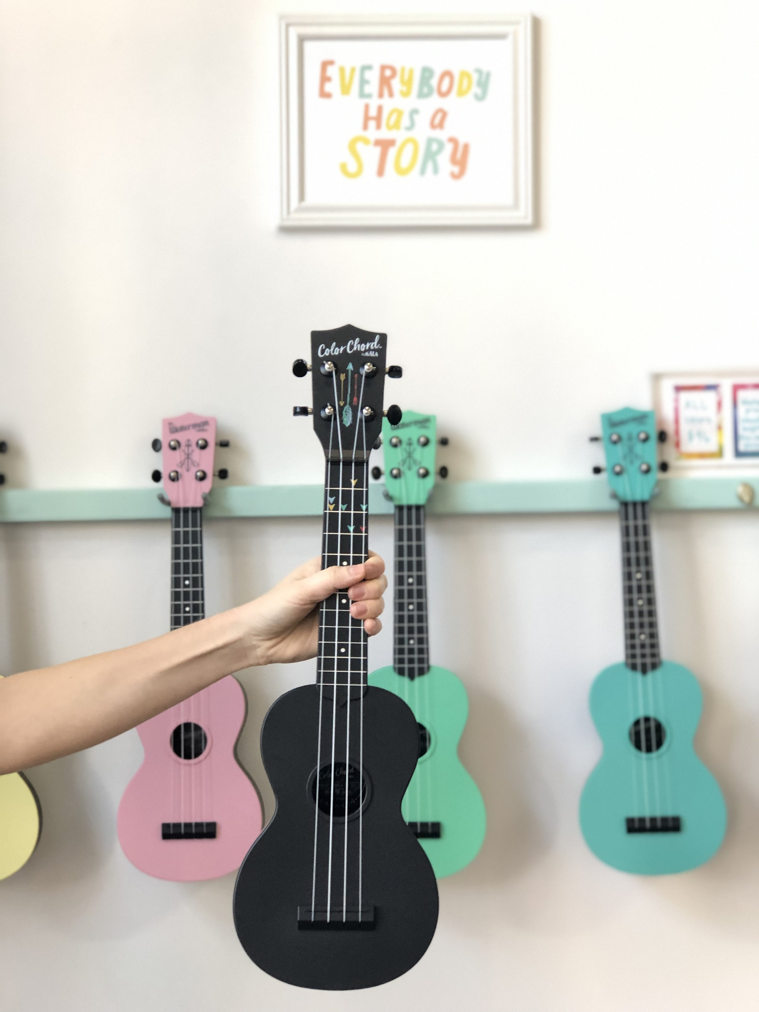 The colorful Waterman ukuleles behind the Color Chord are the same instrument but without the coding system. Life hack: you can use sticky dots from an office supply store to create the color system.