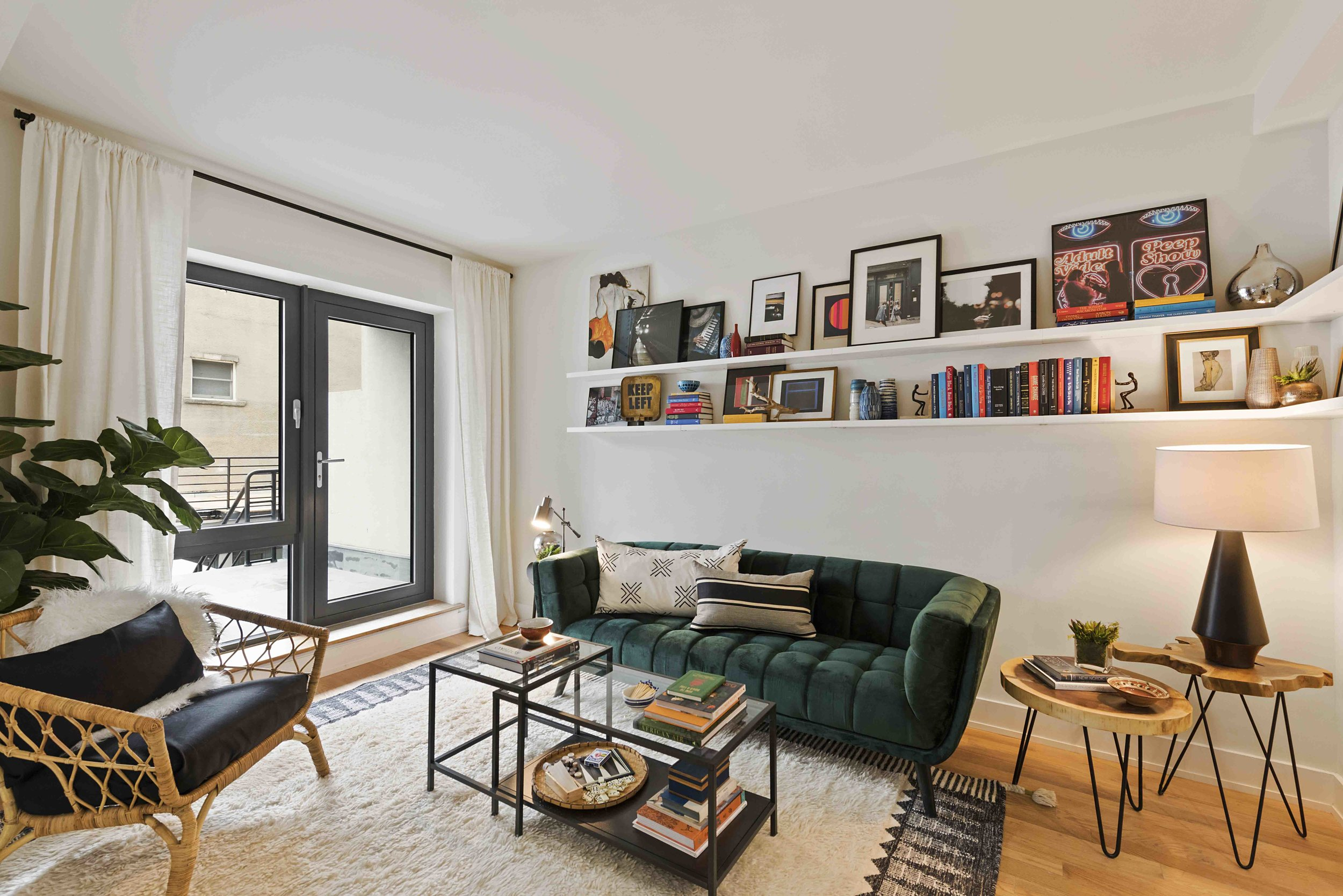 Now talk about color! Not only does the dark green hue of the sofa shine here but the span of color continues along white shelving to pull the eye around this two-story apartment located in Greenpoint, Brooklyn.