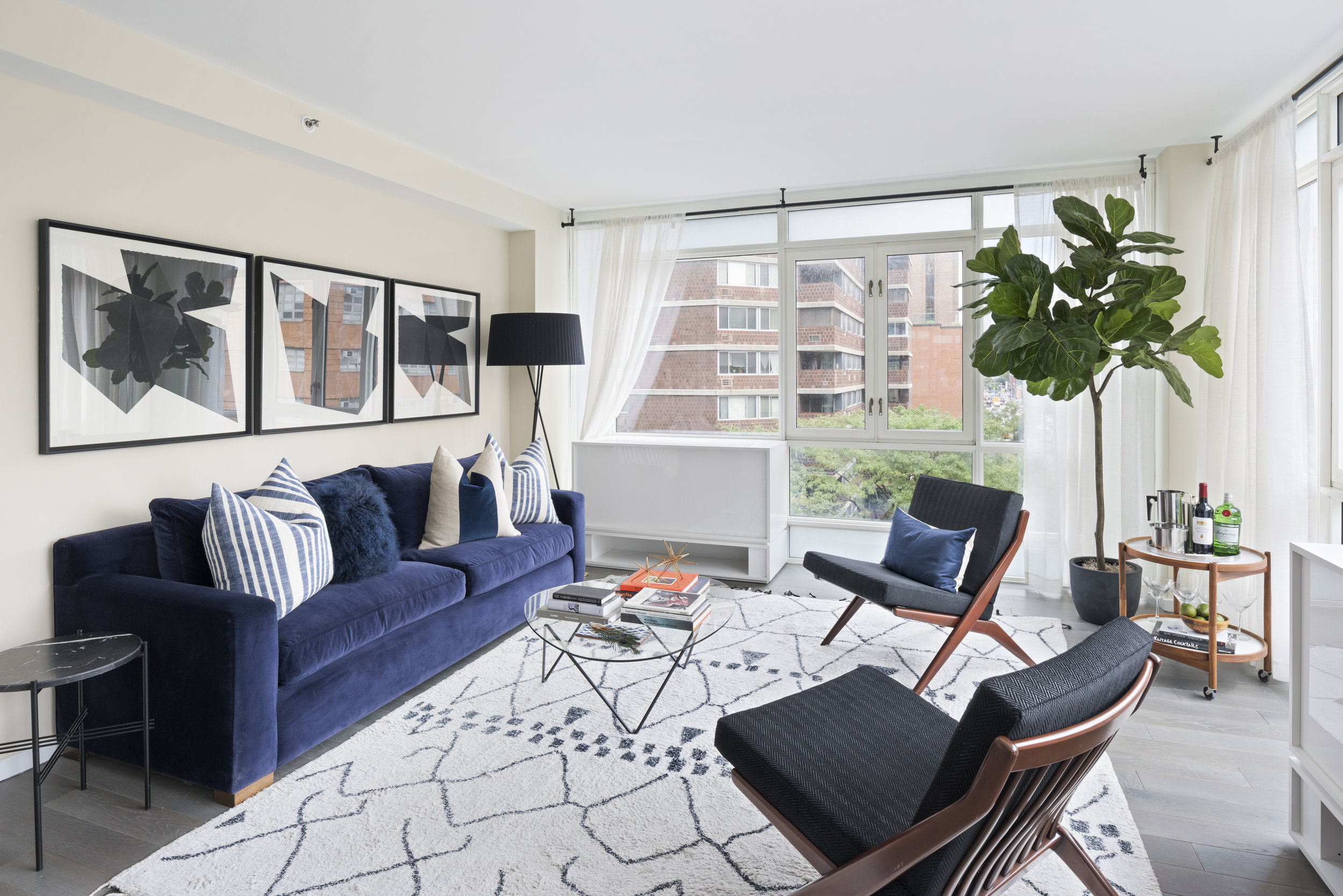 Black and white elements and a neutral rug direct the eye immediately to the blue sofa in this Gramercy Park living space.