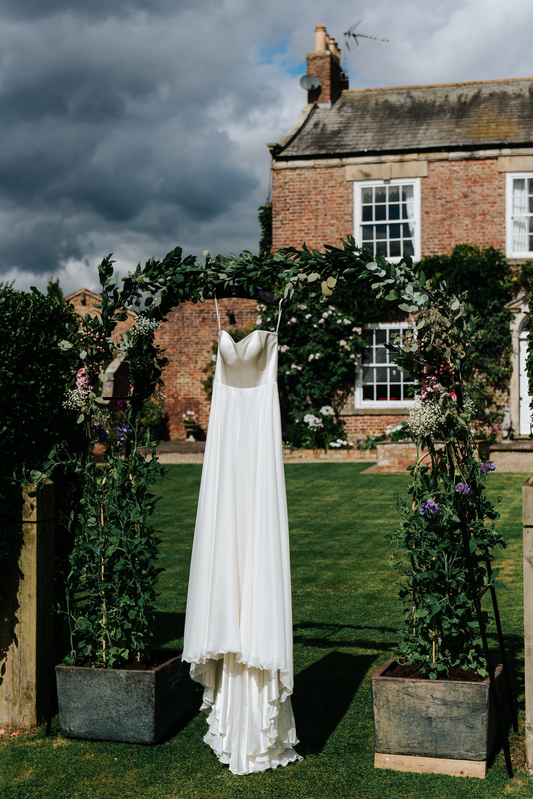 Bride's dress hanging by house