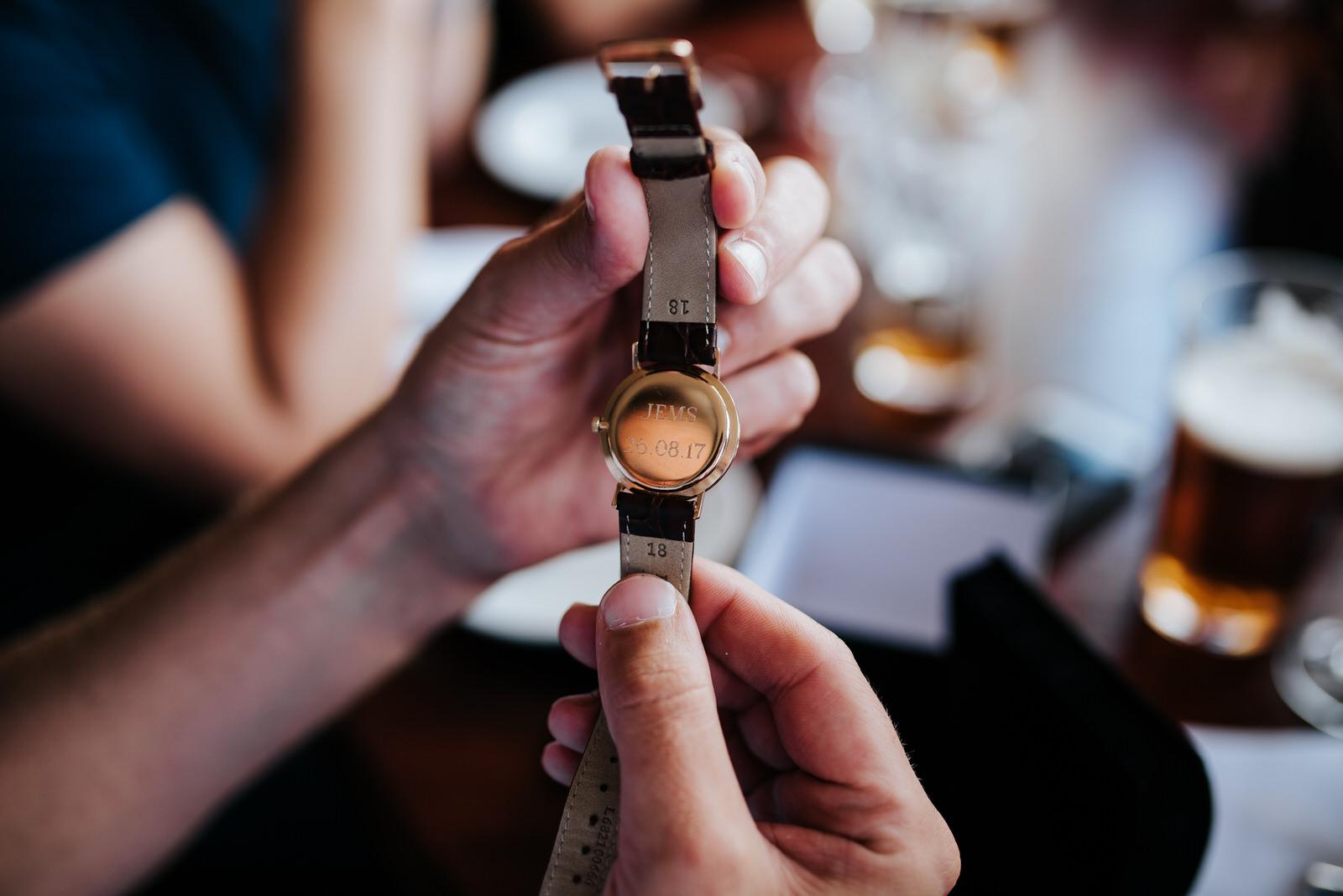 Groom looks at monogrammed watch bride gifted him
