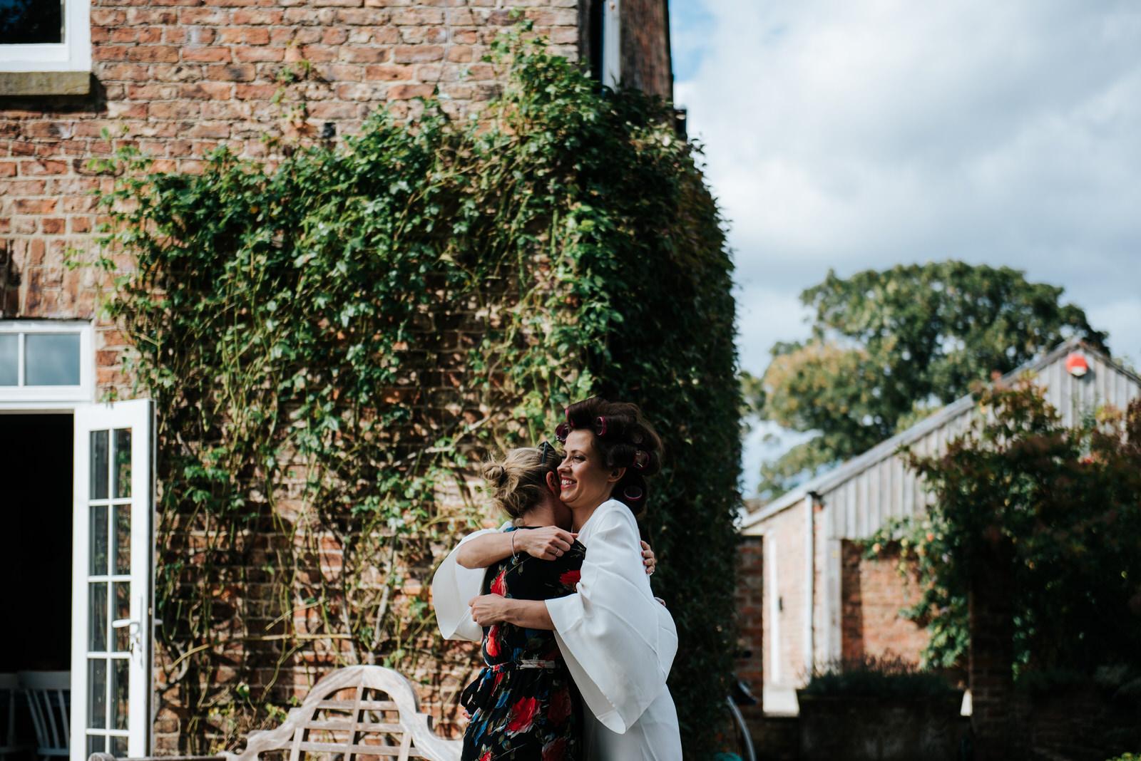 Bride hugs lifelong fround outside house where she gets ready