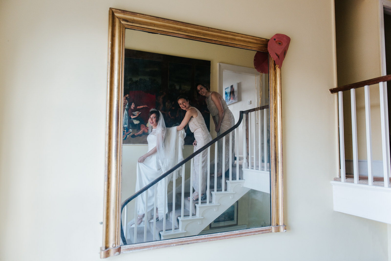 Bride and bridesmaids look into the mirror in awe as they see br