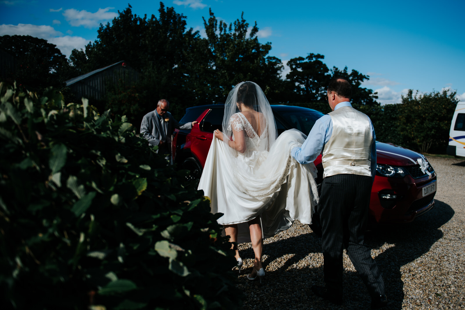 Father of the bride and bride walk towards car which will take t