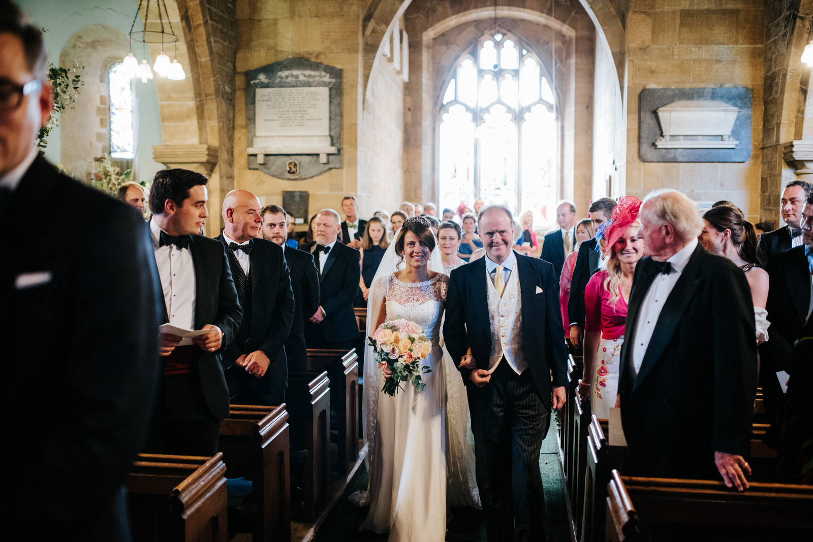 Bride and father of the bride walk down the aisle as everyone lo