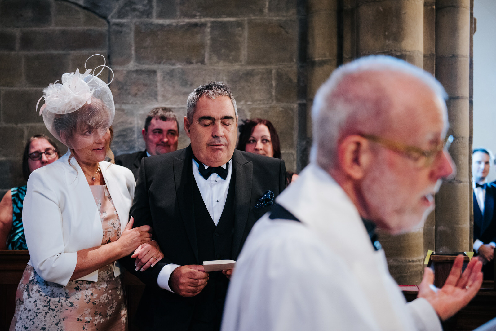 Father of the Groom closes eyes and embraces his wife as the wed