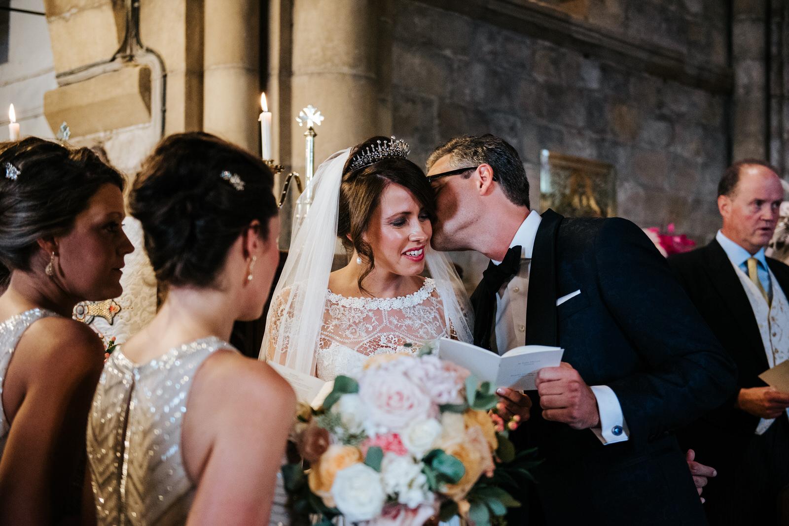 Groom kisses bride on the cheek inside church as readings take p