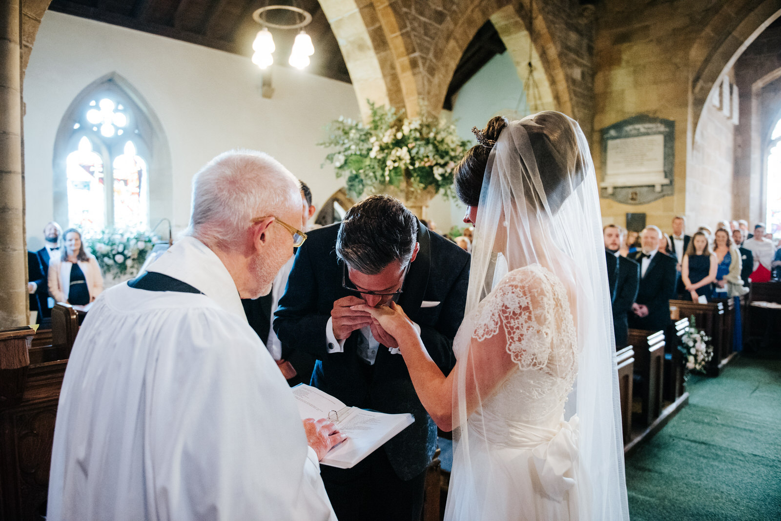 Groom kisses Bride on the finger after putting a ring on it