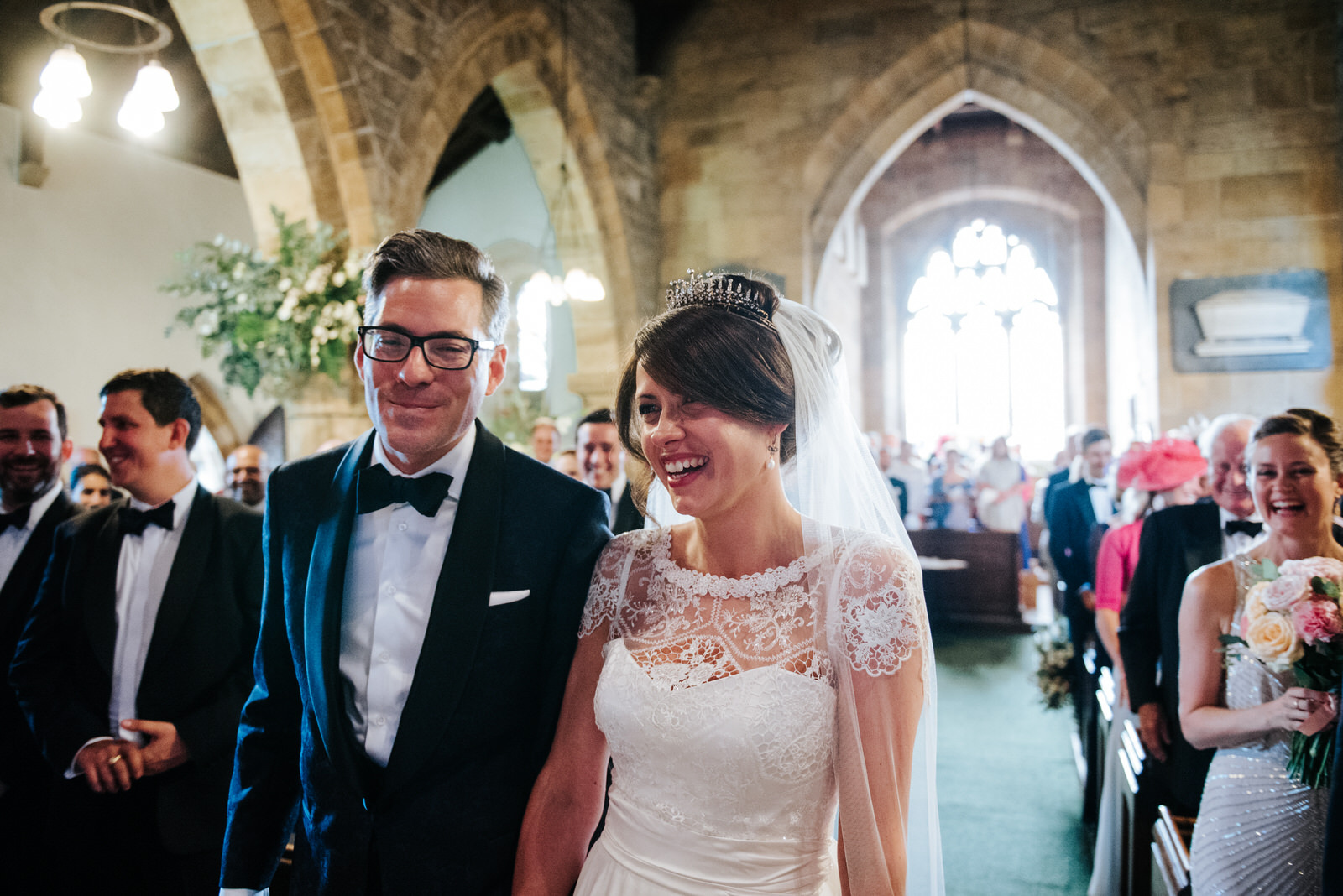 Guests smile at Bride and Groom right after first kiss