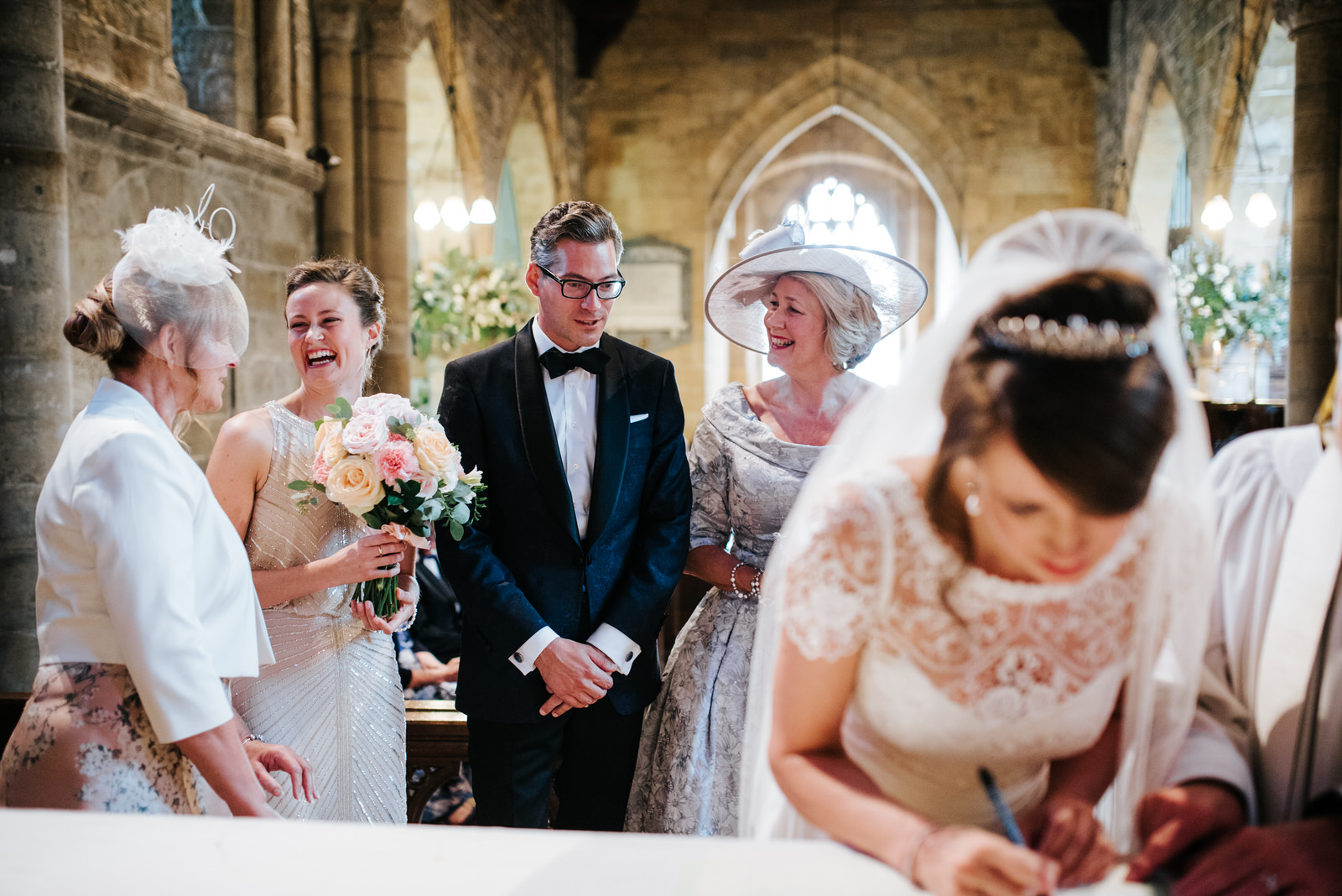 Bride signs the register while Groom and relatives laugh from be