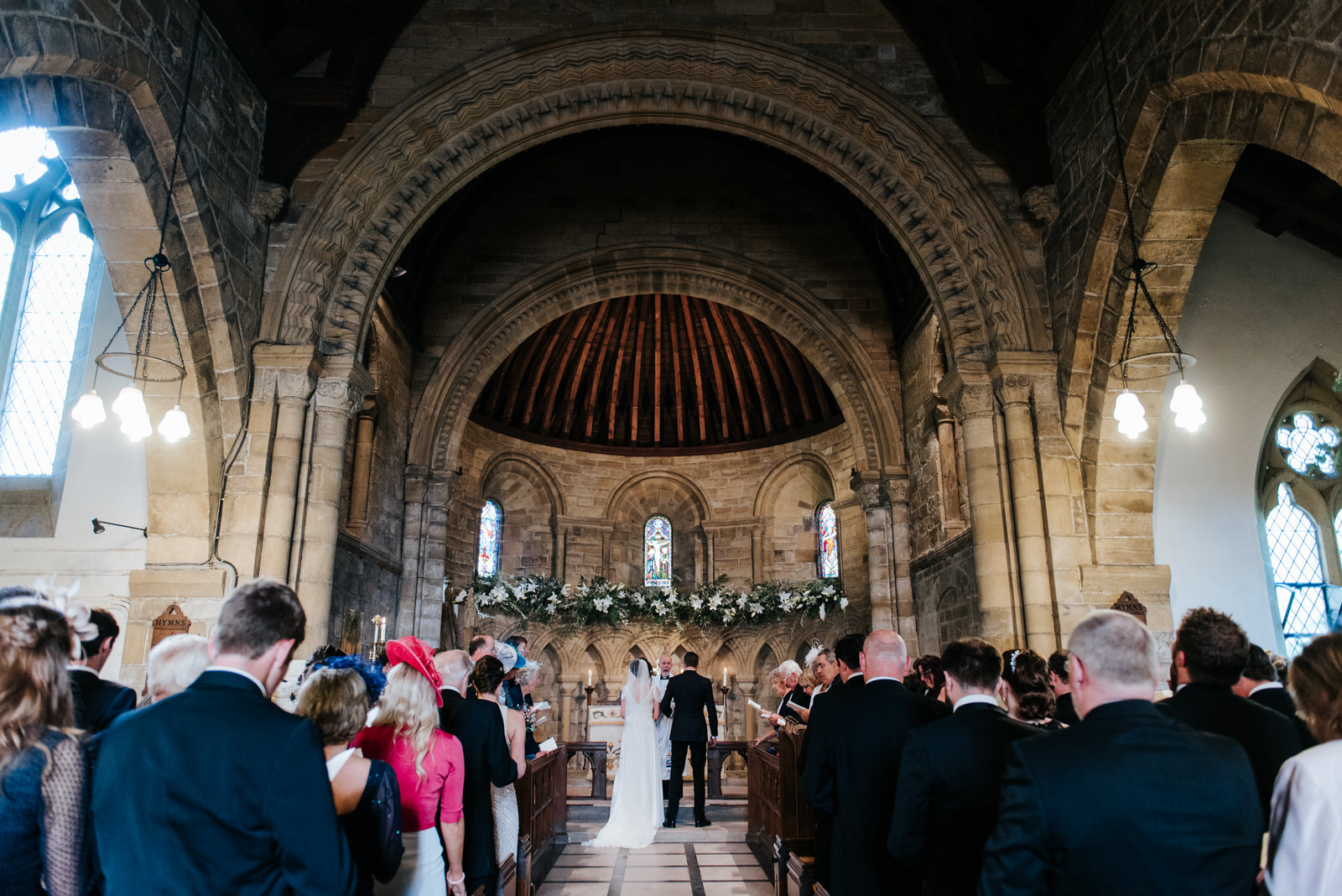 Wide shot of Felixkirk Church interior with Bride and Groom at t