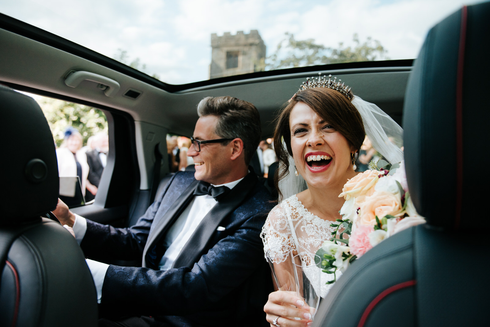 Bride and Groom sit inside car and open bottle of Champagne whil
