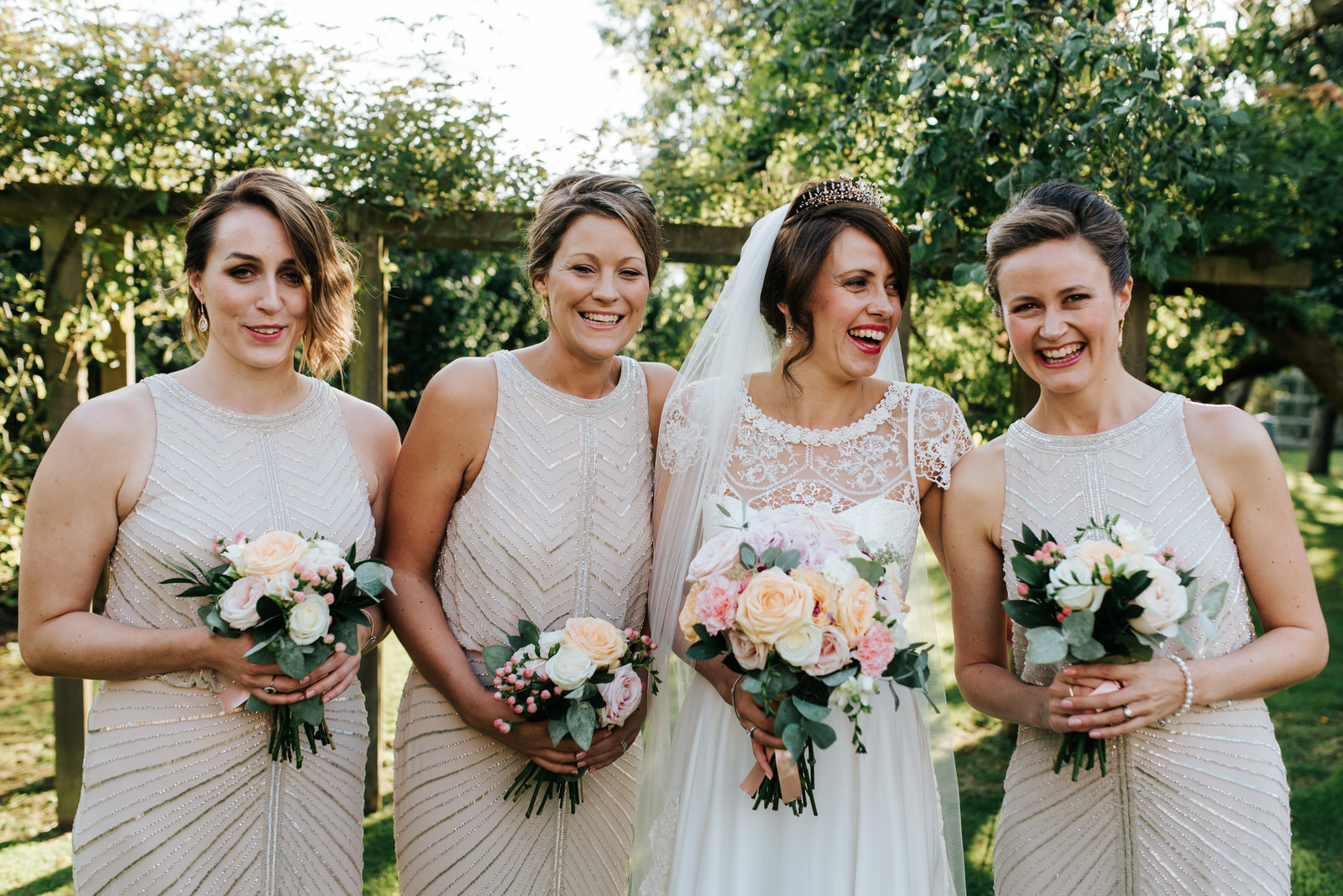 Bride and Bridesmaids smile at camera in stunning garden