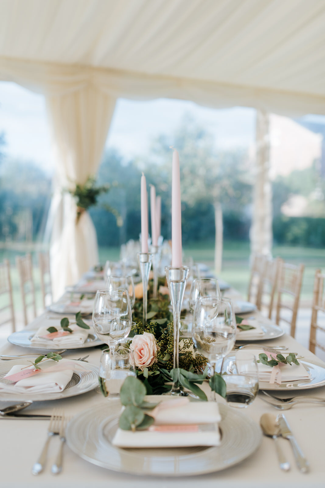 Close-up of table setting inside stunning, tree-lined garden mar
