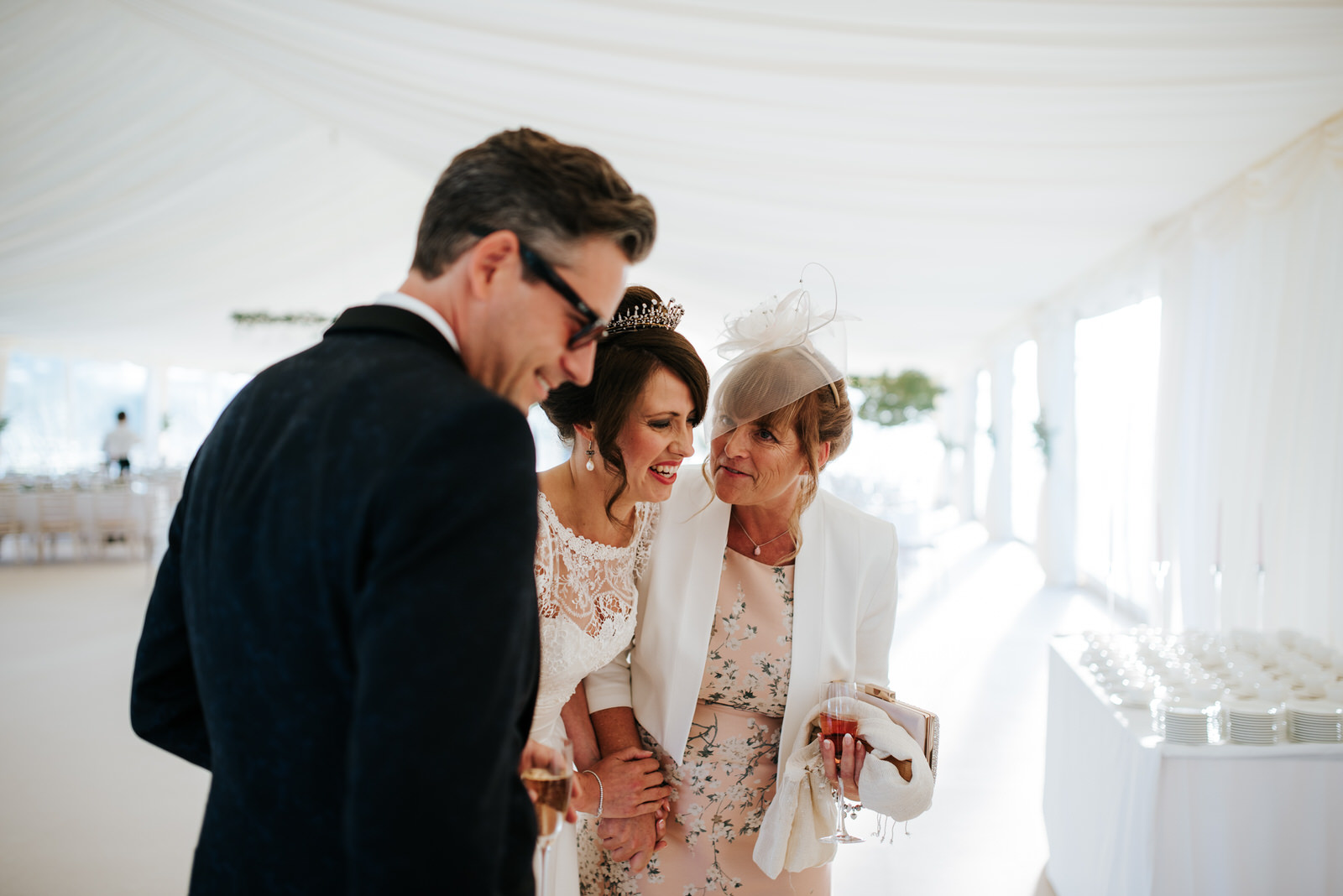 Bride and Groom smile at Mother of the Groom as she hands them a