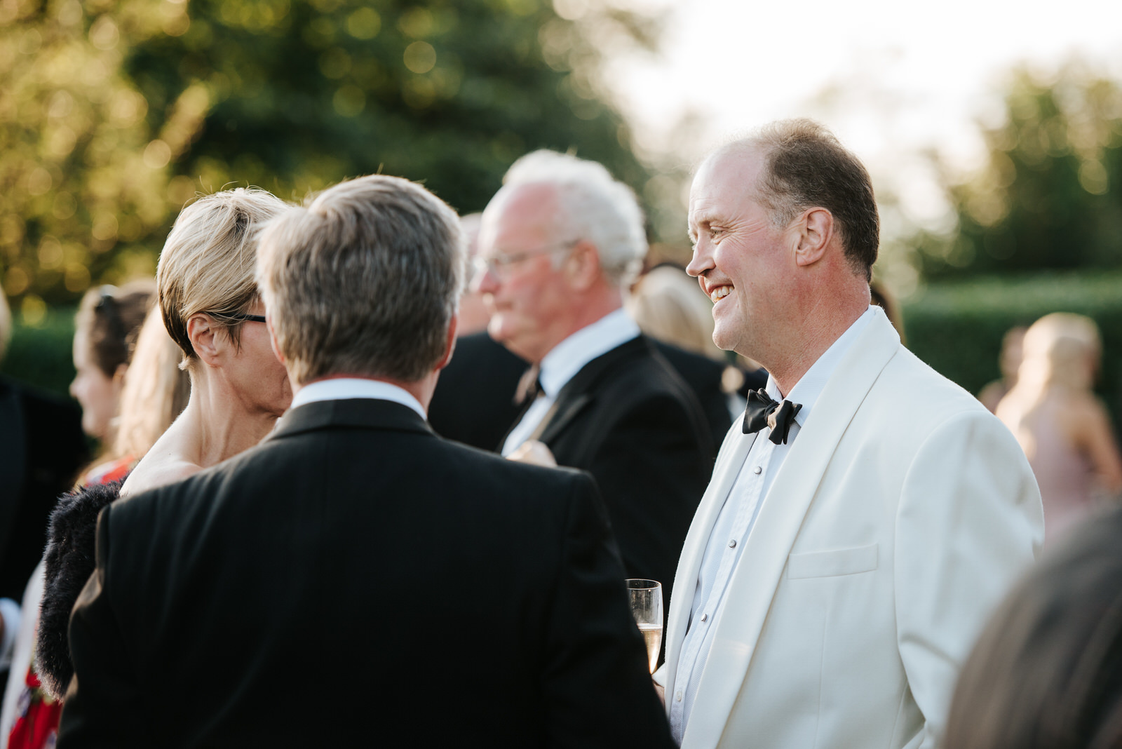 Father of the Bride talks to guests in sun-drenched garden durin