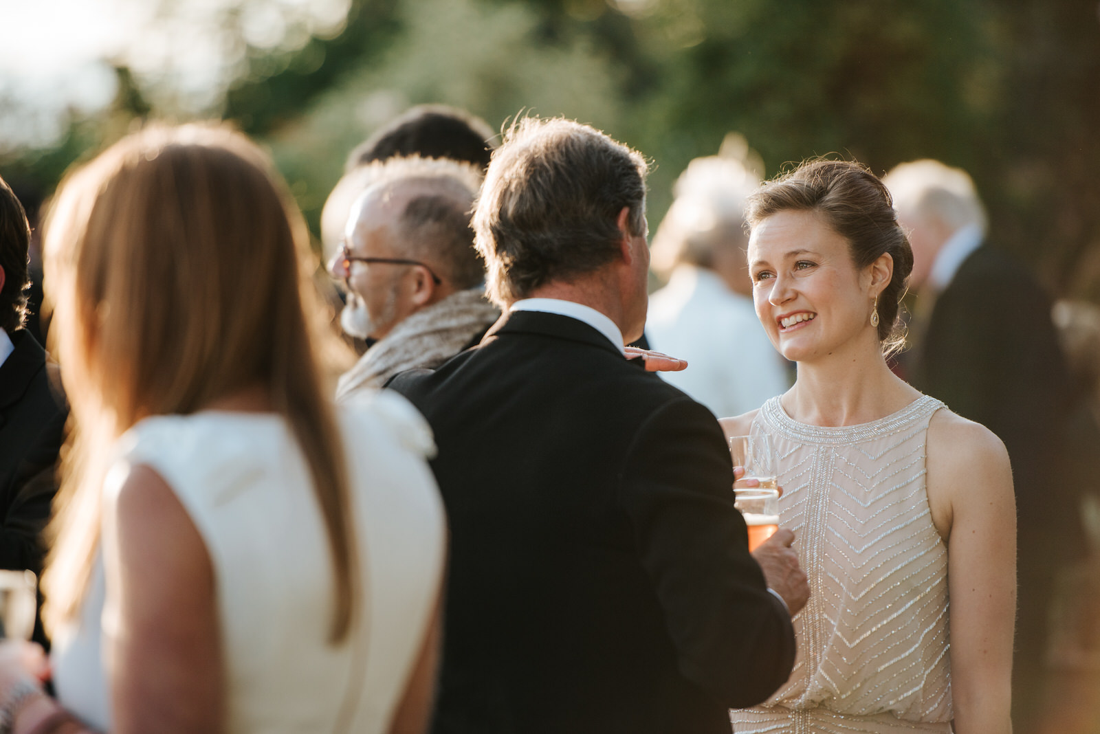 Sister of the Bride smiles in garden as she talks to guests duri