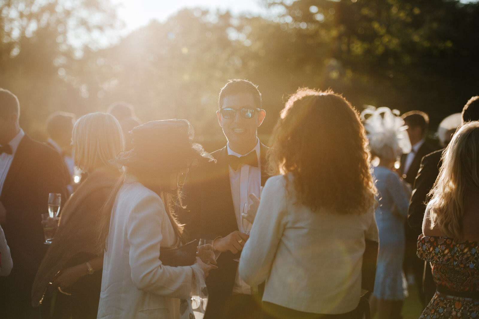 Sun-flare photo of guests talking to each other in garden