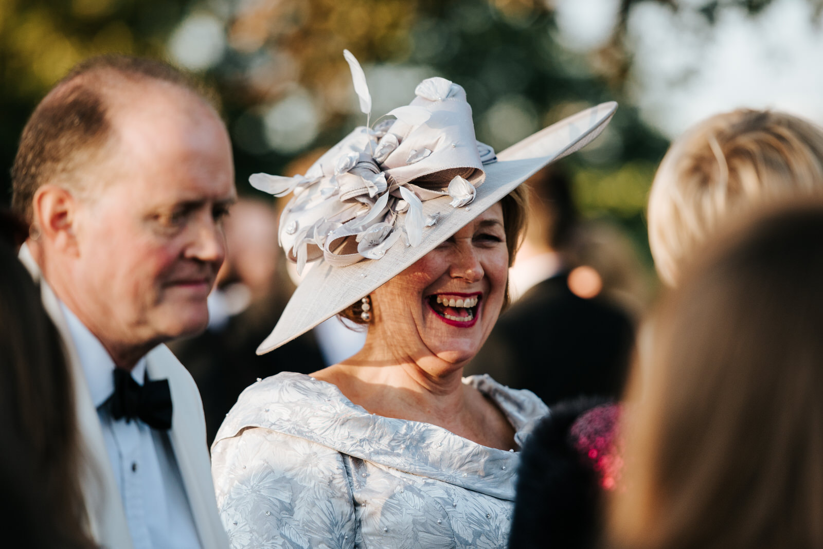 Mother of the bride overjoyed as she wears fabulous hat outside