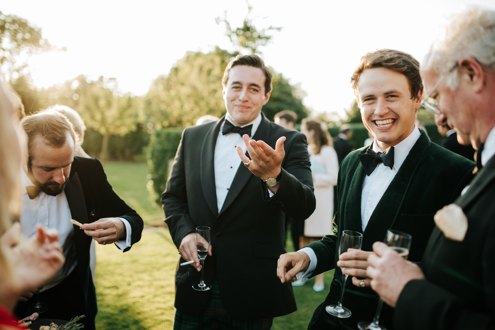Groomsmen share a laugh and a drink during wedding reception in
