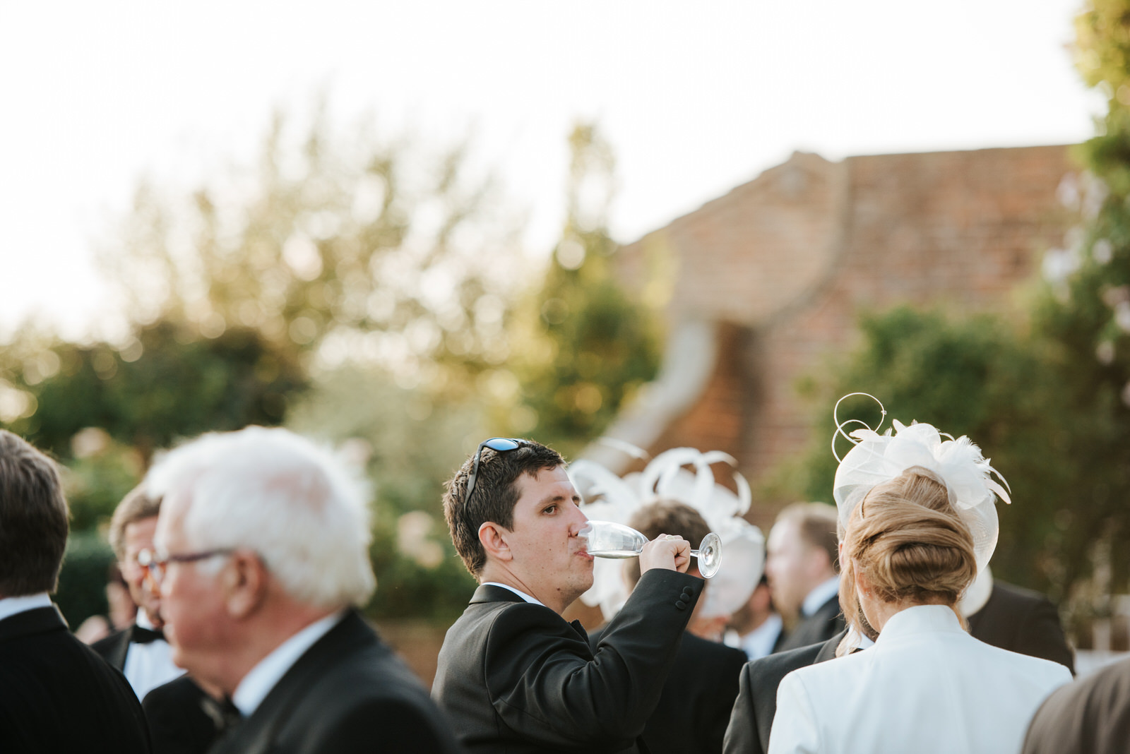 Groom's best man drinks champagne in beautiful, green garden wed