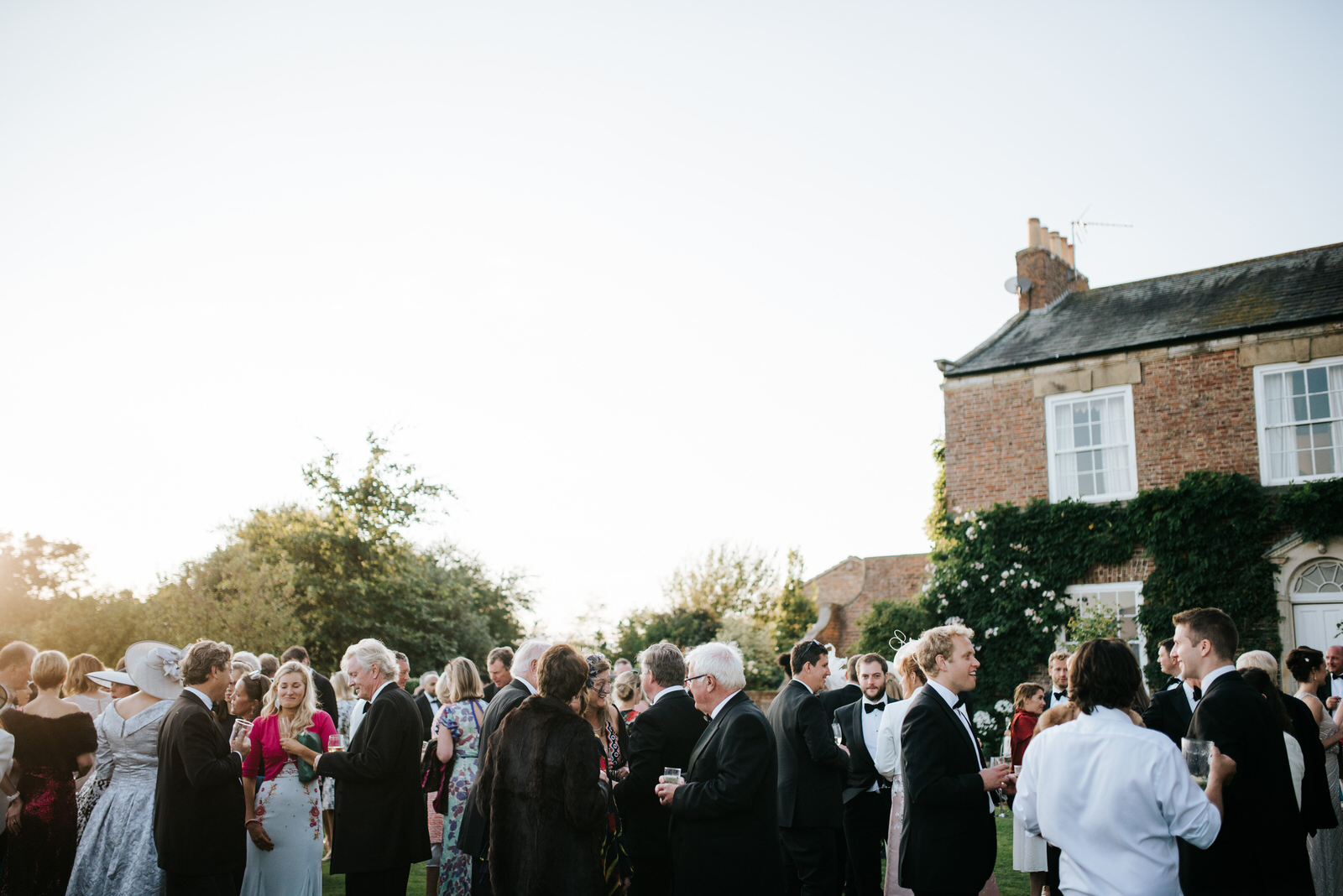 Wide shot of guests enjoying themselves during garden wedding re