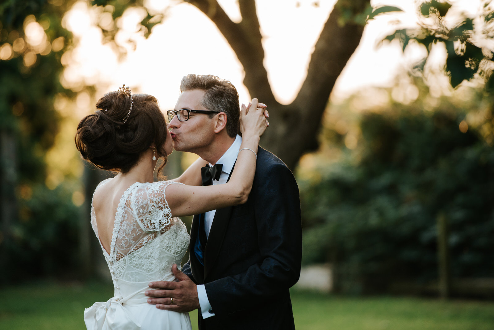 Bride and groom kiss in front of tree during portraits as sun se