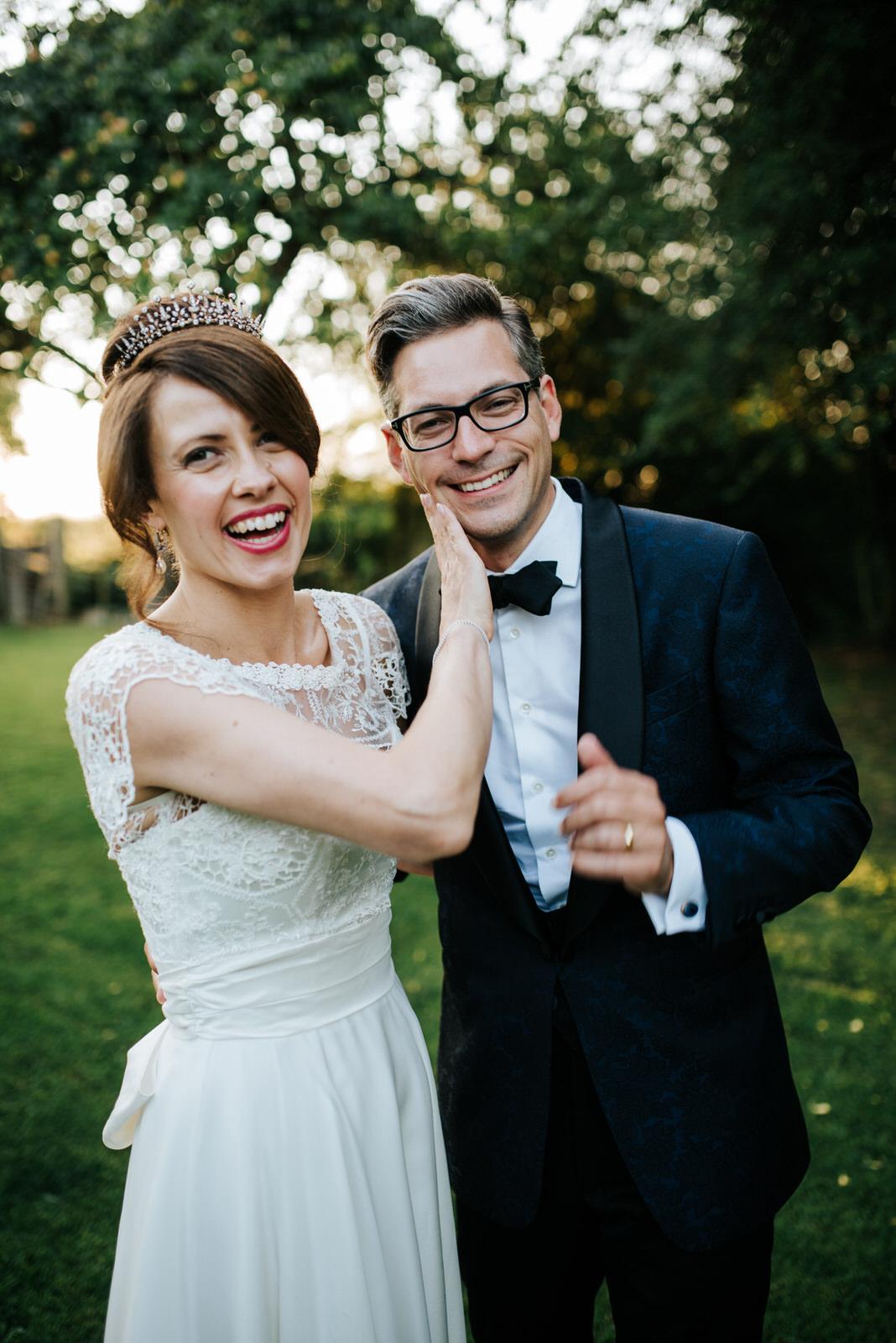 Bride rubs lipstick off Groom in orchard next to wedding recepti