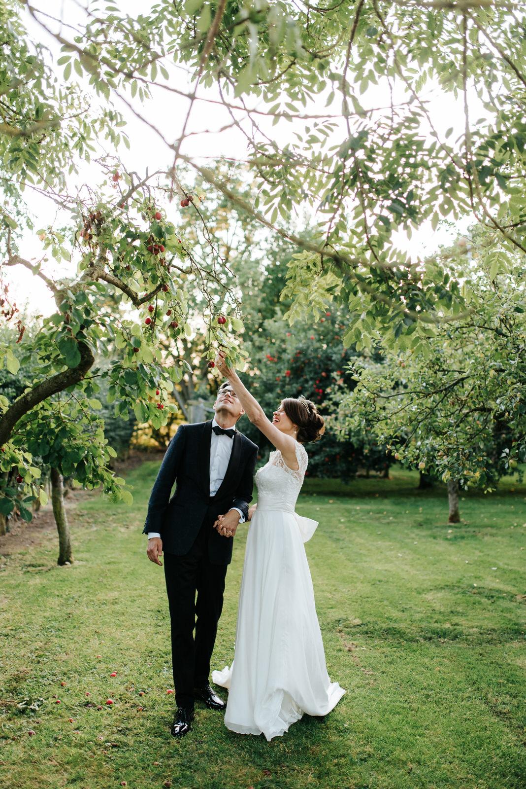 Bride and Groom standing under Plum tree in Yorkshire