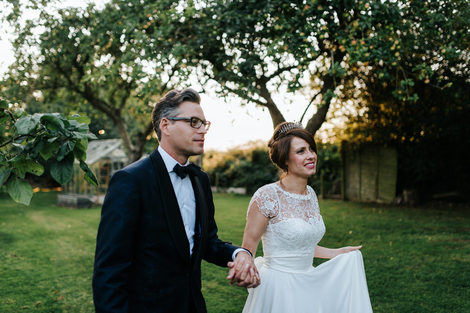 Bride and Groom walk towards guests in sun-drenched garden