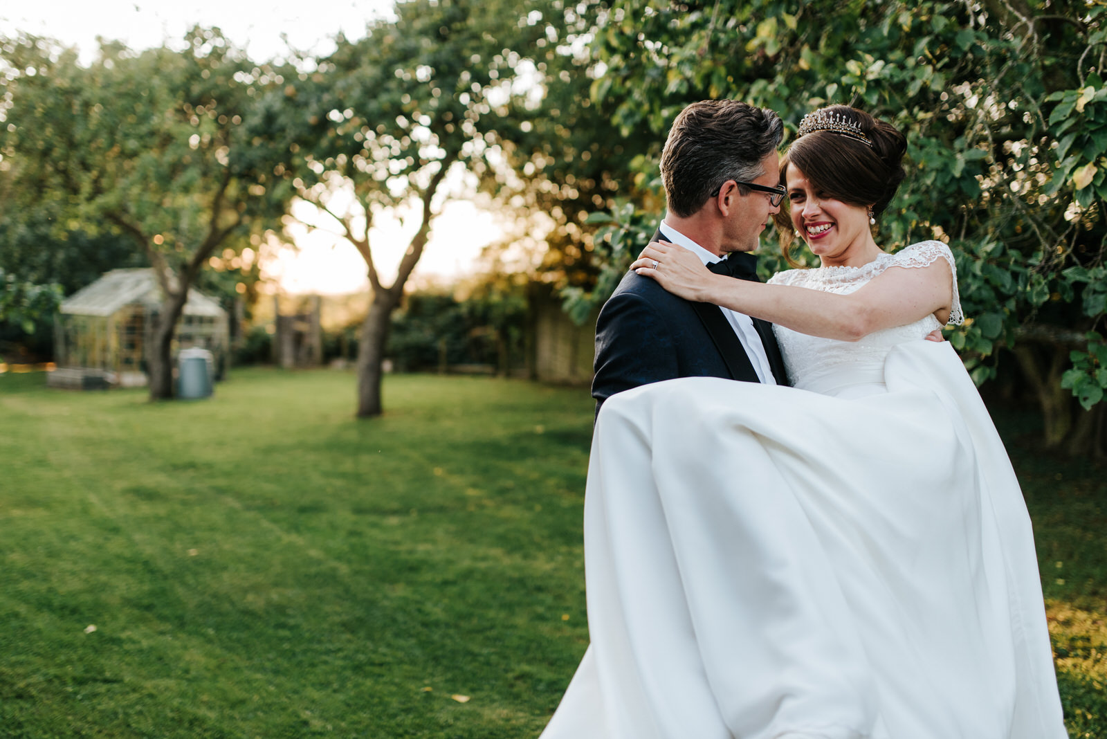 Bride lifted up by Groom as they smile at each other in beautifu