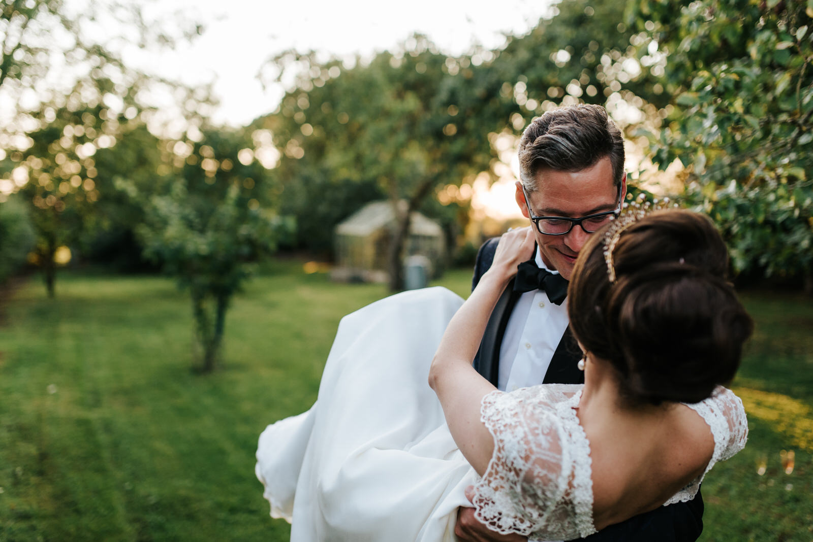 Groom dips bride while she grabs onto his neck during sunset pho