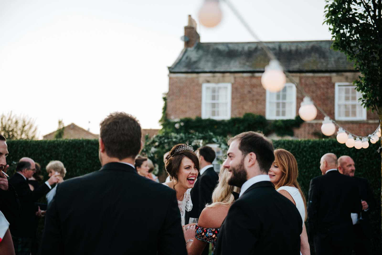 Bride laughs loudly in front of house as wedding reception ends