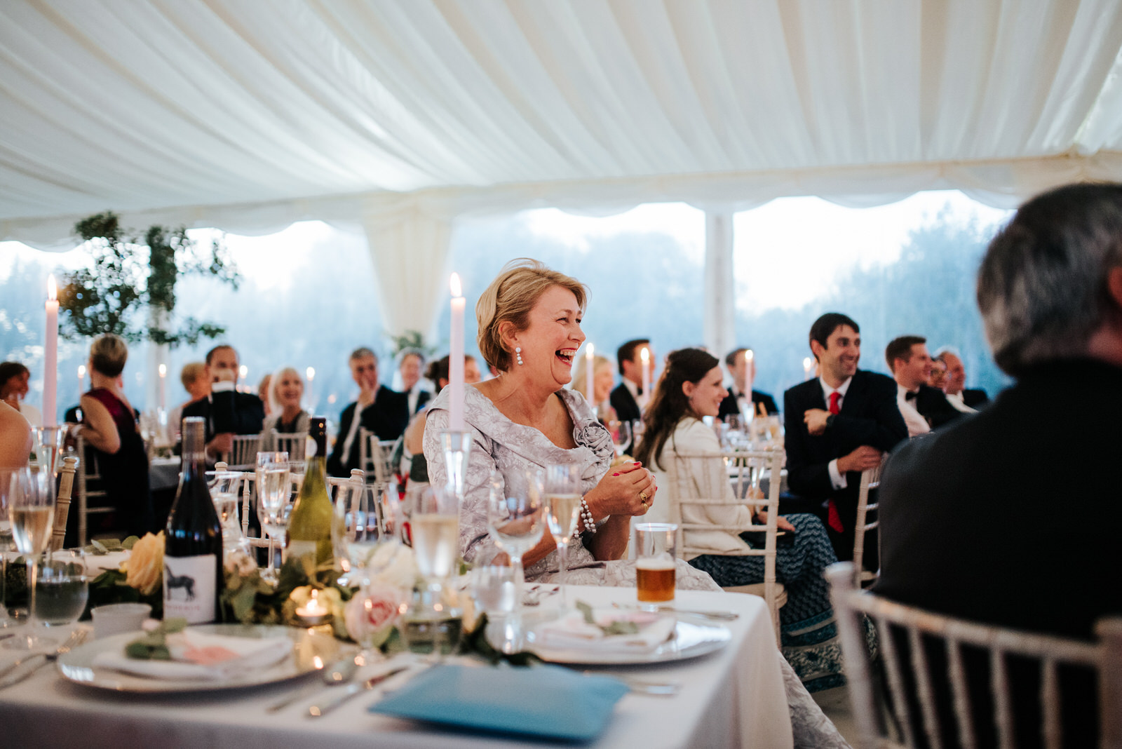 Mother of the Bride smiles during speeches inside Marquee