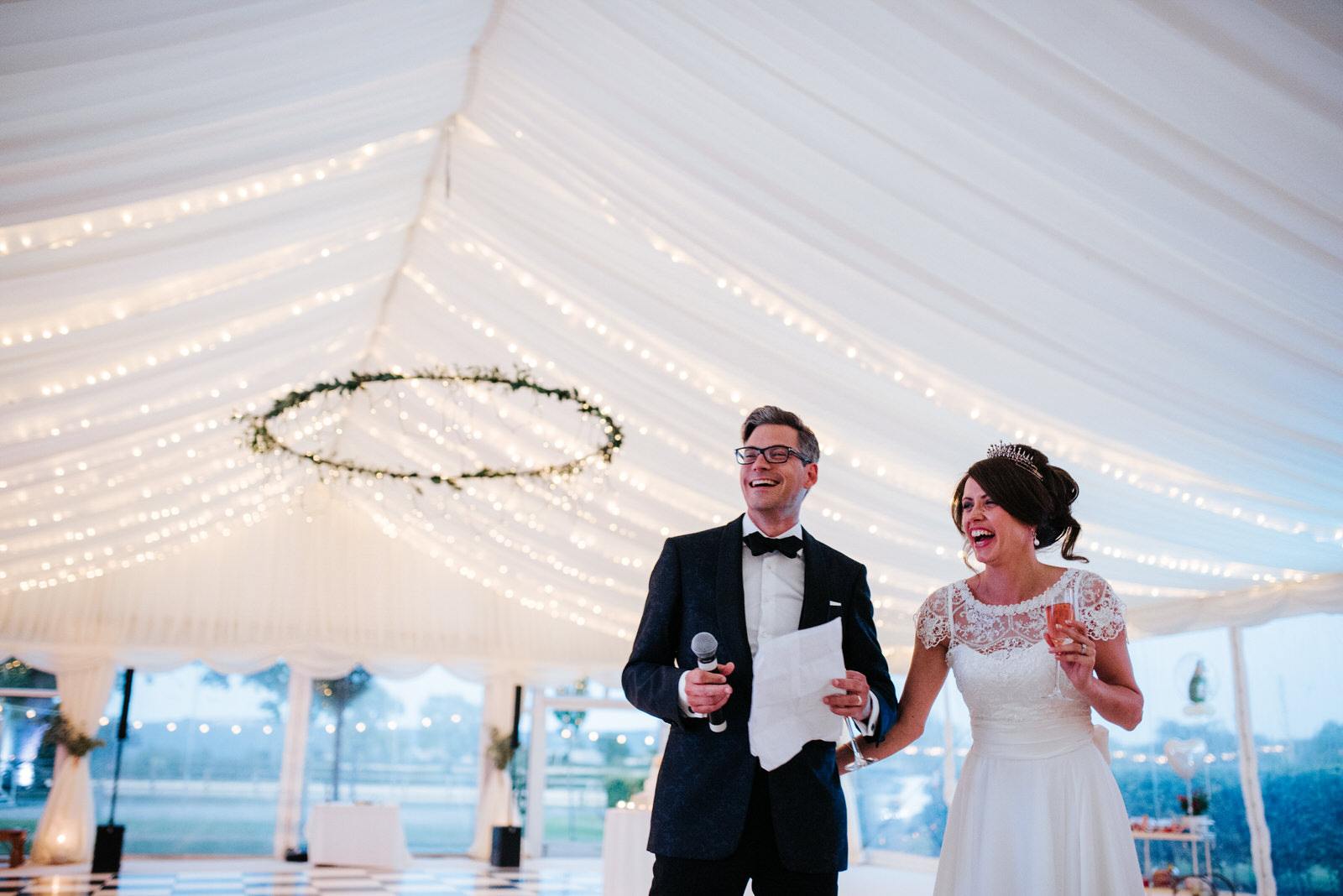 Bride and Groom laugh into the distance as Groom concludes speec