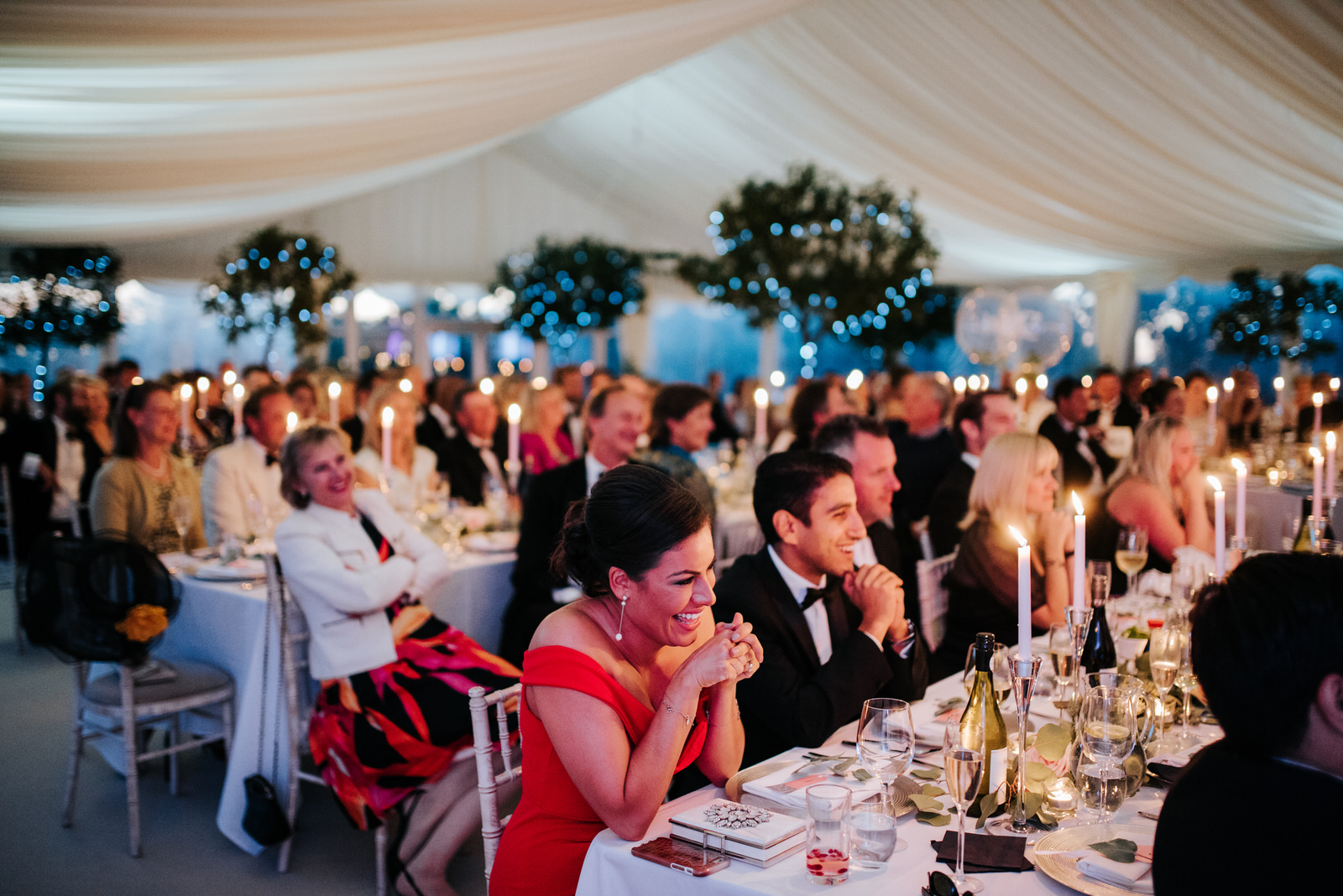Guests are amused as speeches are delivered in candle-lit marque