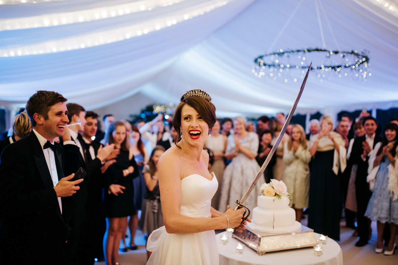 Bride holds military sword after cutting wedding cake as guests