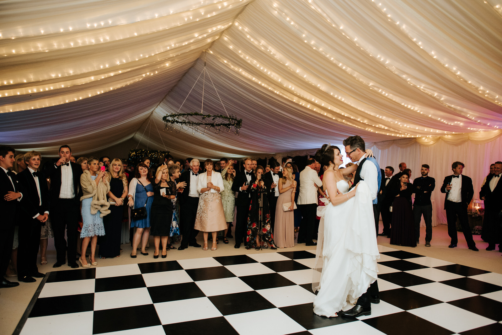 Wide shot of bride and groom embracing each other during their f