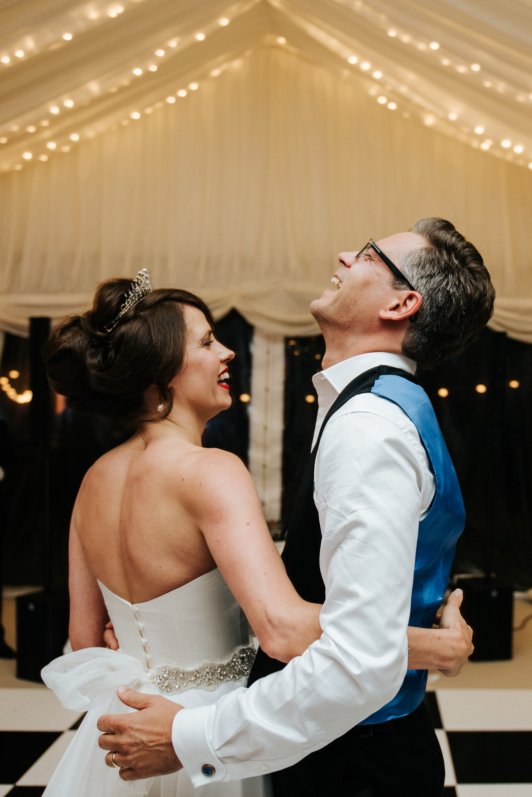Bride and groom smile and laugh as first dance inside garden mar