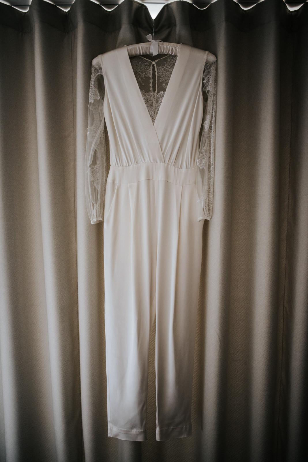 Bride's two-piece handmade wedding dress hanging by the window