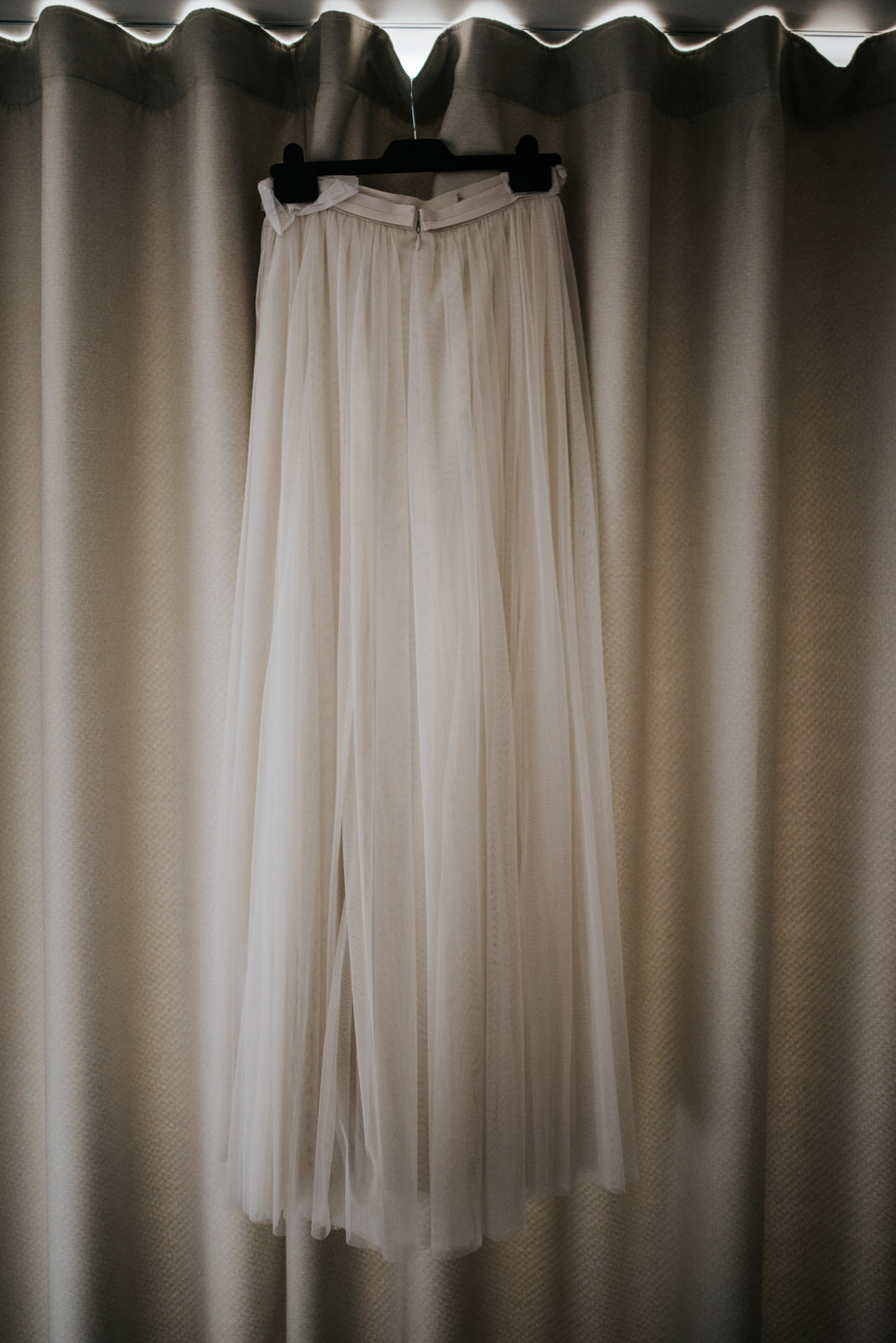 Bride's wedding skirt hanging by the window