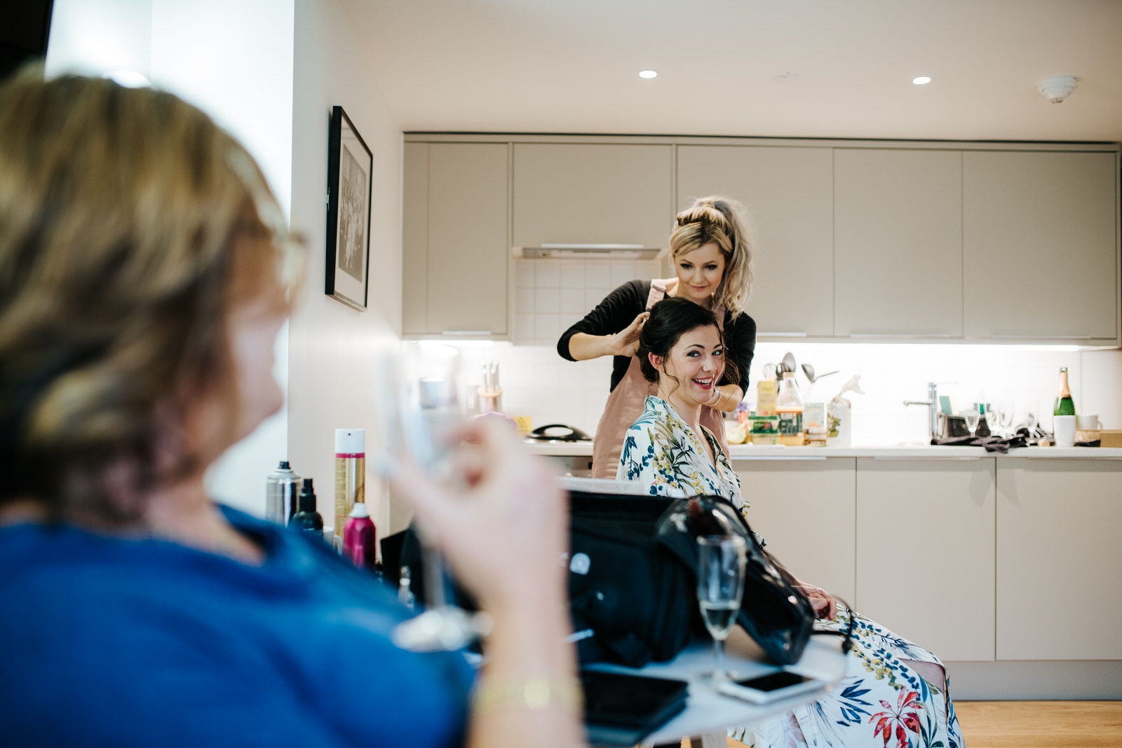 Bride getting her hair done while laughing and looking at mother